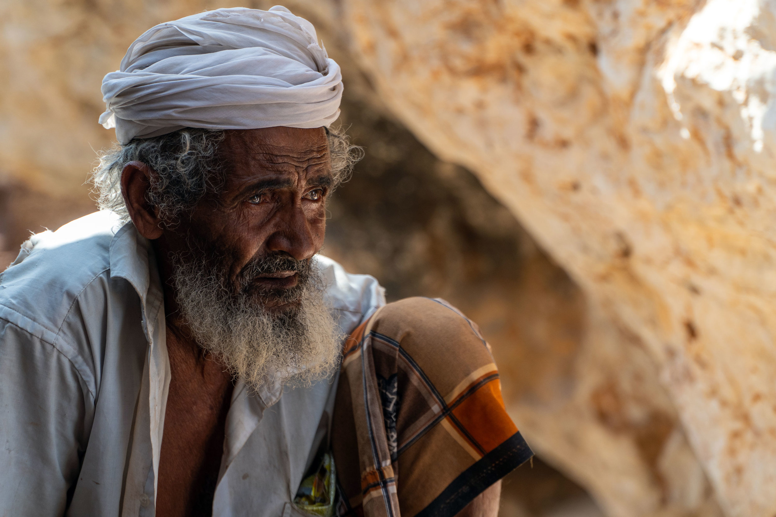 A Socotri elder takes a rest in his stone shelter in the remote Shu'ab region of far western Socotra. Accessible only by sea and hiking, Shu'ab is a remote community of Socotri bedouin who primarily raise goats. This man brings his herd to graze on the grasses along the coastline every day, drinking tea and smoking his tobacco pipe in his shelter before beginning the trek back to the village in the afternoon.