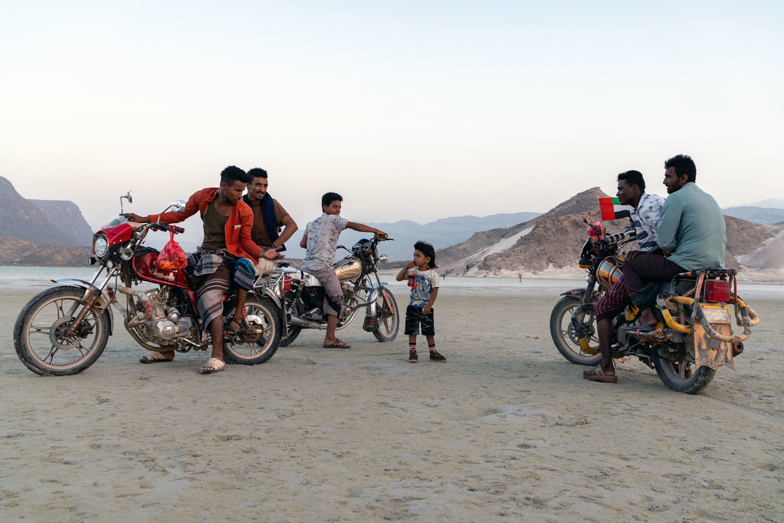 "A group of young Socotri men ride around the coast on their motorcycles. Note the Emirati flag on the bike on the right; the UAE and Saudi Arabia have been providing aid and reconstruction projects on the island since the war in Yemen started, including a UAE military base. While certainly not a full ""take over"", the UAE flag can be seen all around the island, along with the flags of Yemen and the former flag of South Yemen."