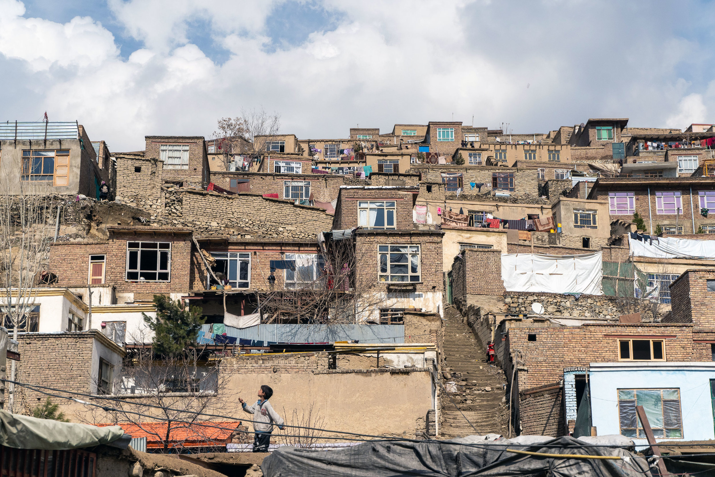 "A boy ""running kites"" in one of Kabul's many hillside neighbourhoods."