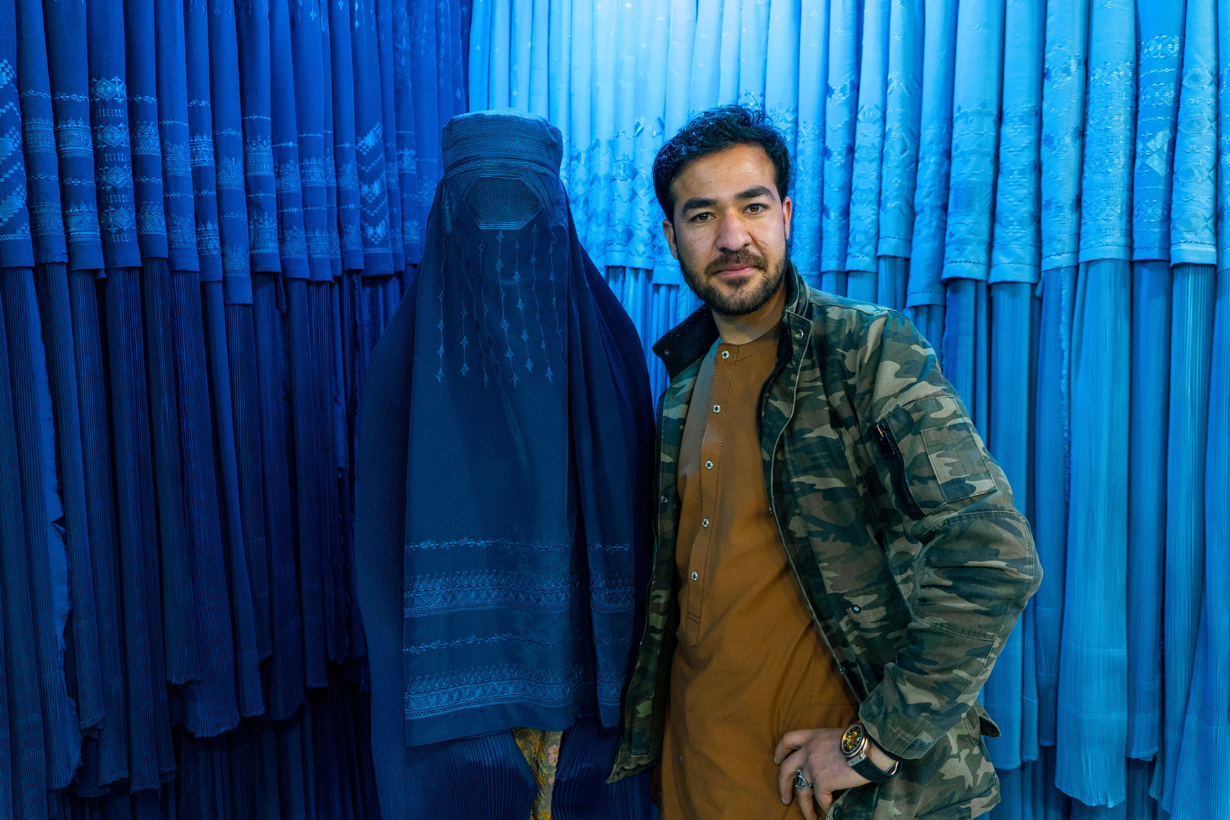 A  chadri  (burqa) salesman poses next to his newest customer at a burqa shop in the northern city of Mazar-i Sharif. The  chadri  has been worn by Pashtun women since before Islam arrived in Afghanistan. While it became a rare to see the garment in the cities during the swinging 60s, during the Taliban years the  chadri  was made mandatory for women to wear in public. Today is is relatively common still, although there is significantly more choice for women in urban areas of Afghanistan.