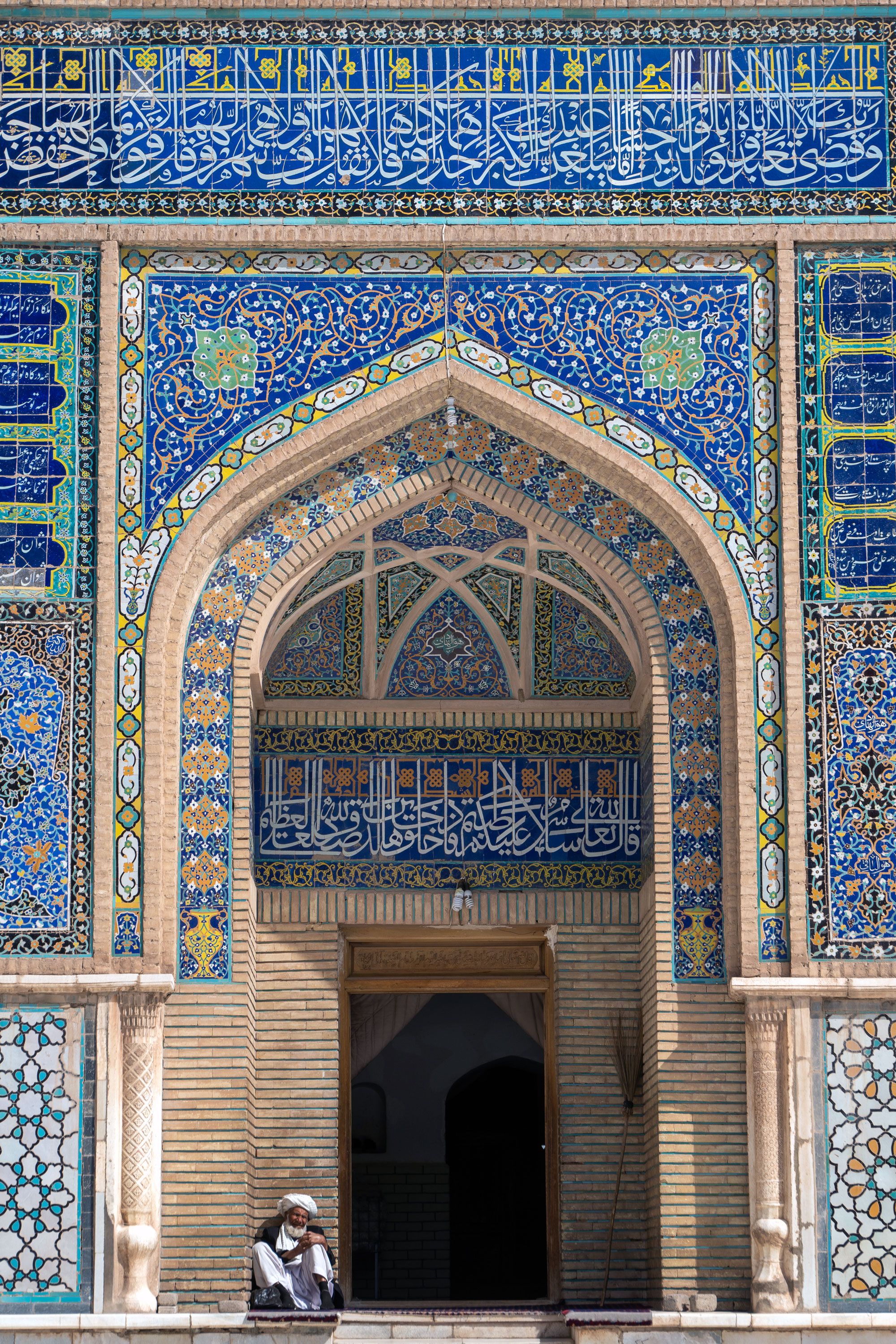 An old man sits under an archway at the colourful Friday Mosque in Herat.