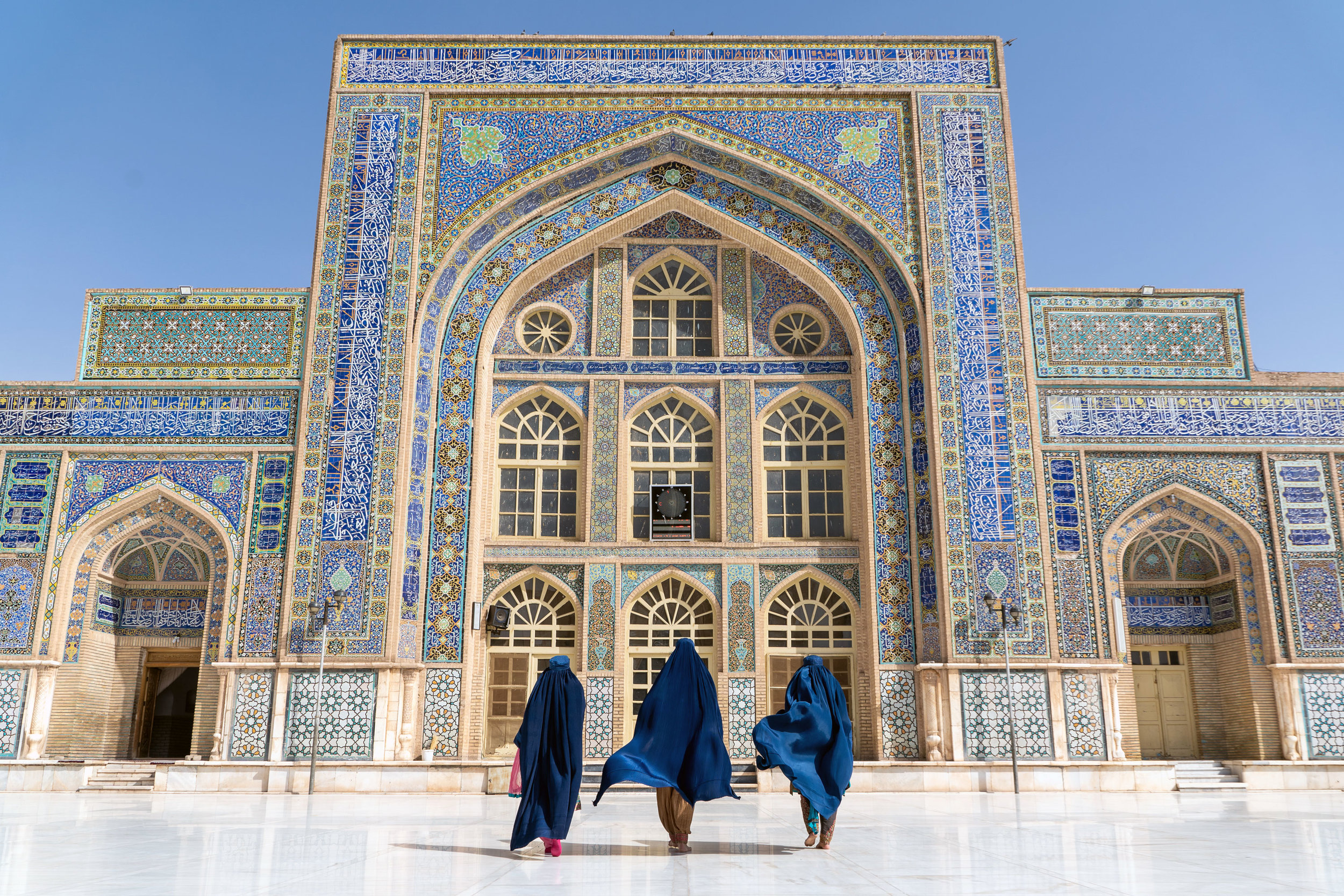 Three women in blue  chadris  walk in front of the interior of Herat's Friday Mosque.