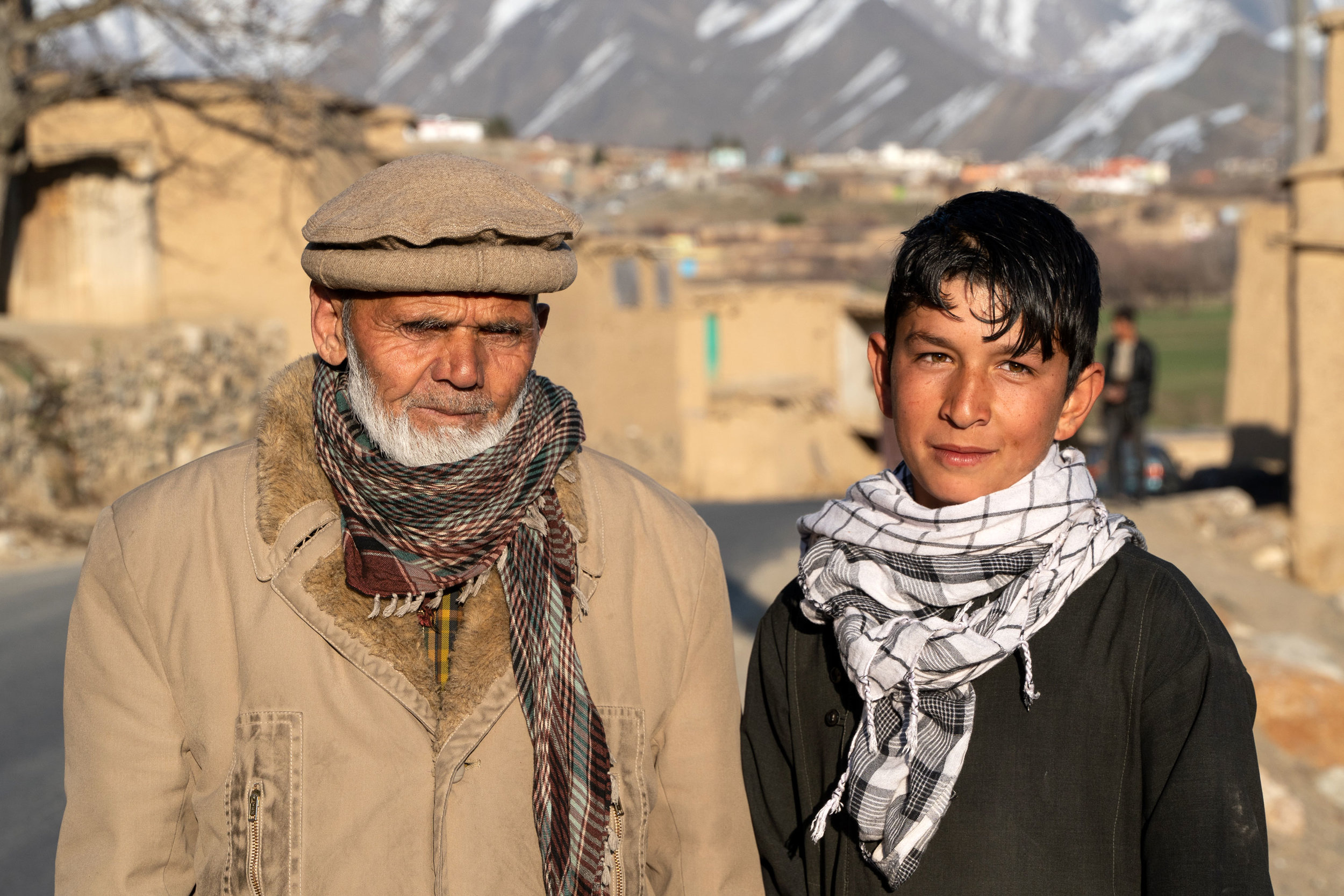 An ethnic Tajik grandfather and grandson pose for s sunset picture in Parwan Province's Panjshir Valley. The Panjshir is part of the Tajik heartland in Afghanistan and was the home of the Tajik mujahid fighter Ahmed Shah Masood, who defended the valley and Afghanistan's northeast from the Taliban. He was later killed in a terrorist attack in 2001, and his mausoleum is here in the Panjshir.