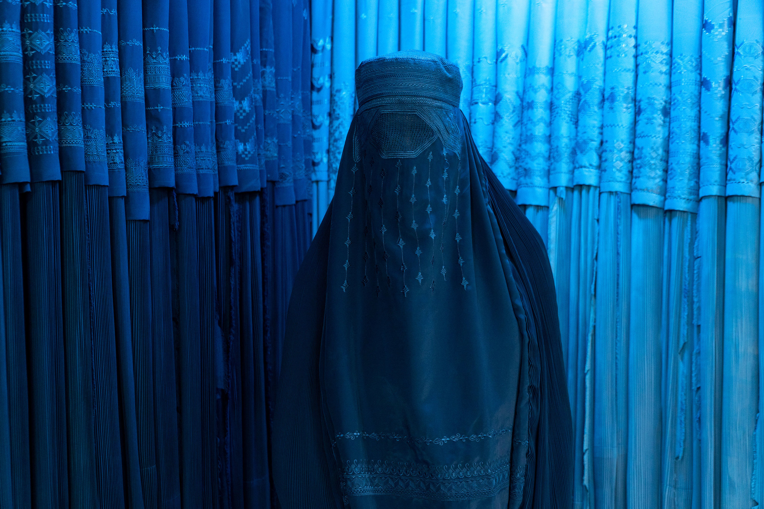 Perhaps the most ubiquitous symbol of Afghanistan's women is the  chadri , or commonly called a  burqa  in the West ( burqa  is the Arabic term, whereas  chadri  is Dari/Persian). Here, a woman poses in a burqa shop in thee northern city of Mazar-i-Sharif. While no longer mandatory, many women in Afghanistan choose to wear the burqa out of safety and protection, while others do so out of a sense of obligation, and others may be forced to by their families. The debate rages on domestically as to the place for this piece of clothing.
