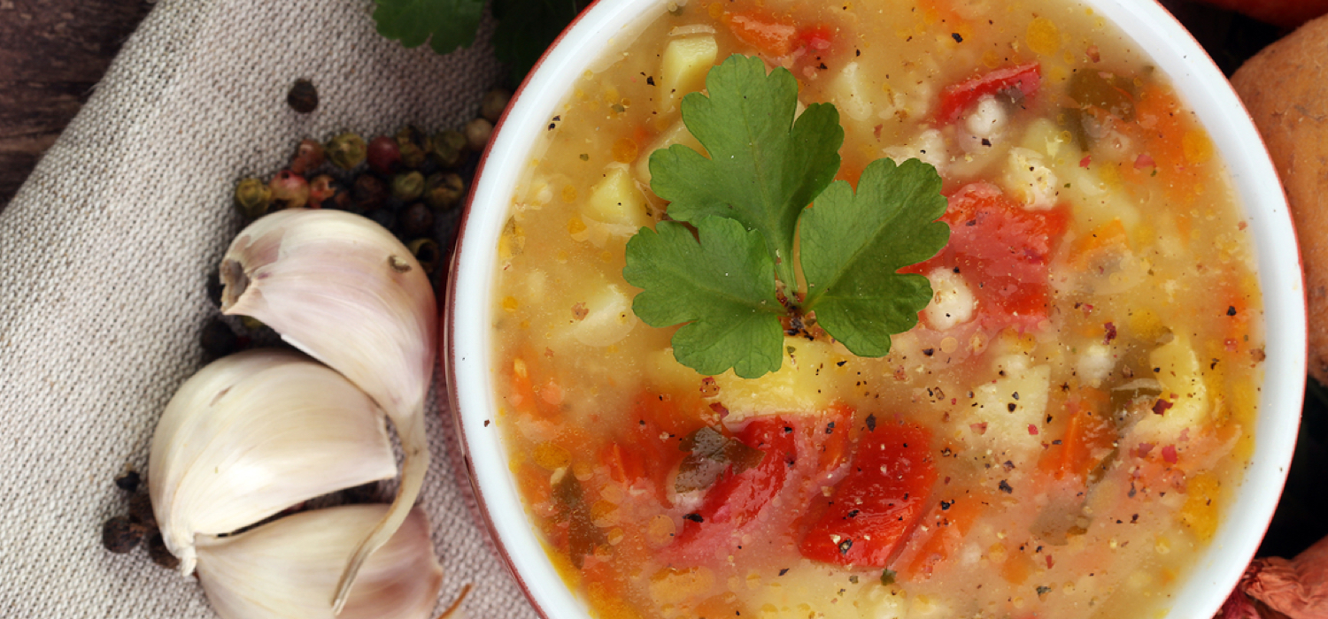 Vegtable-soup-in-bowl-on-table-with-galic.jpg