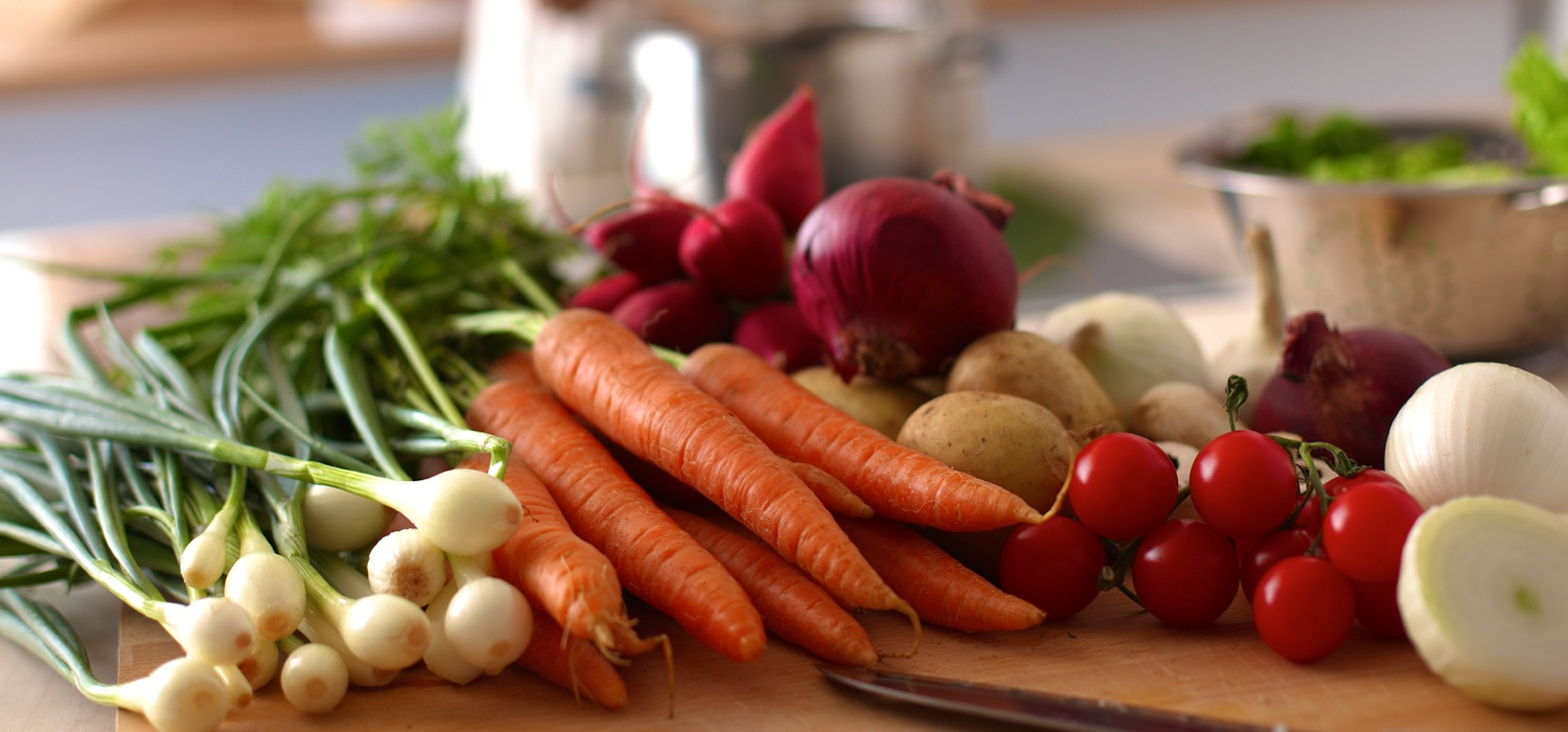 a-bunch-of-carrots-onions-potoas-tomatos-greens-in-kitchen.jpg