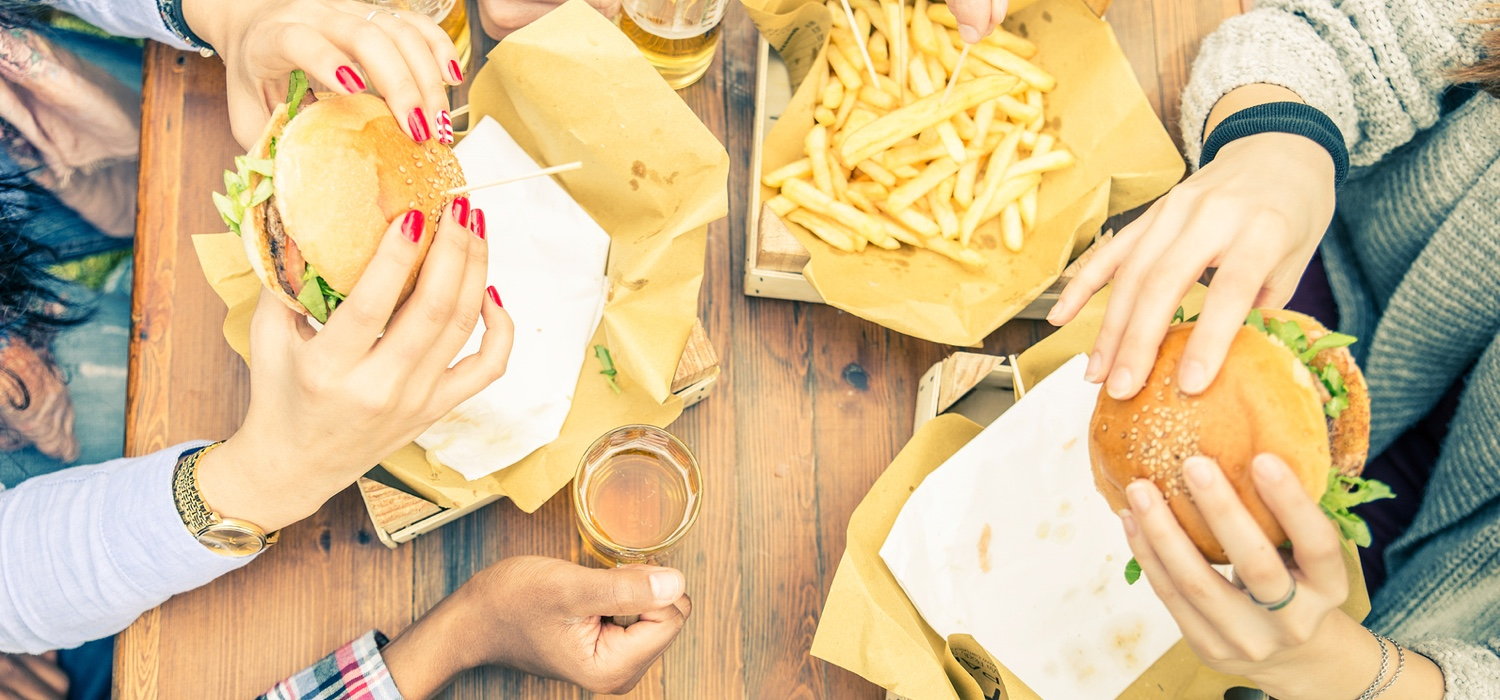 friends-eating-burgers-french-fries-and-beer-together.jpg