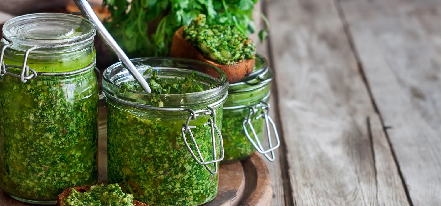 Homemade cilantro-pesto-in-jars-on-wooden-background.jpg