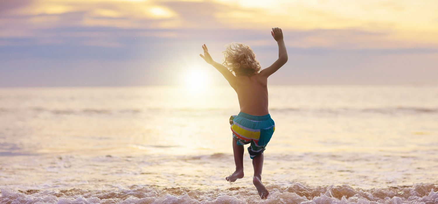 Boy jumping at the beach in the summer.jpg