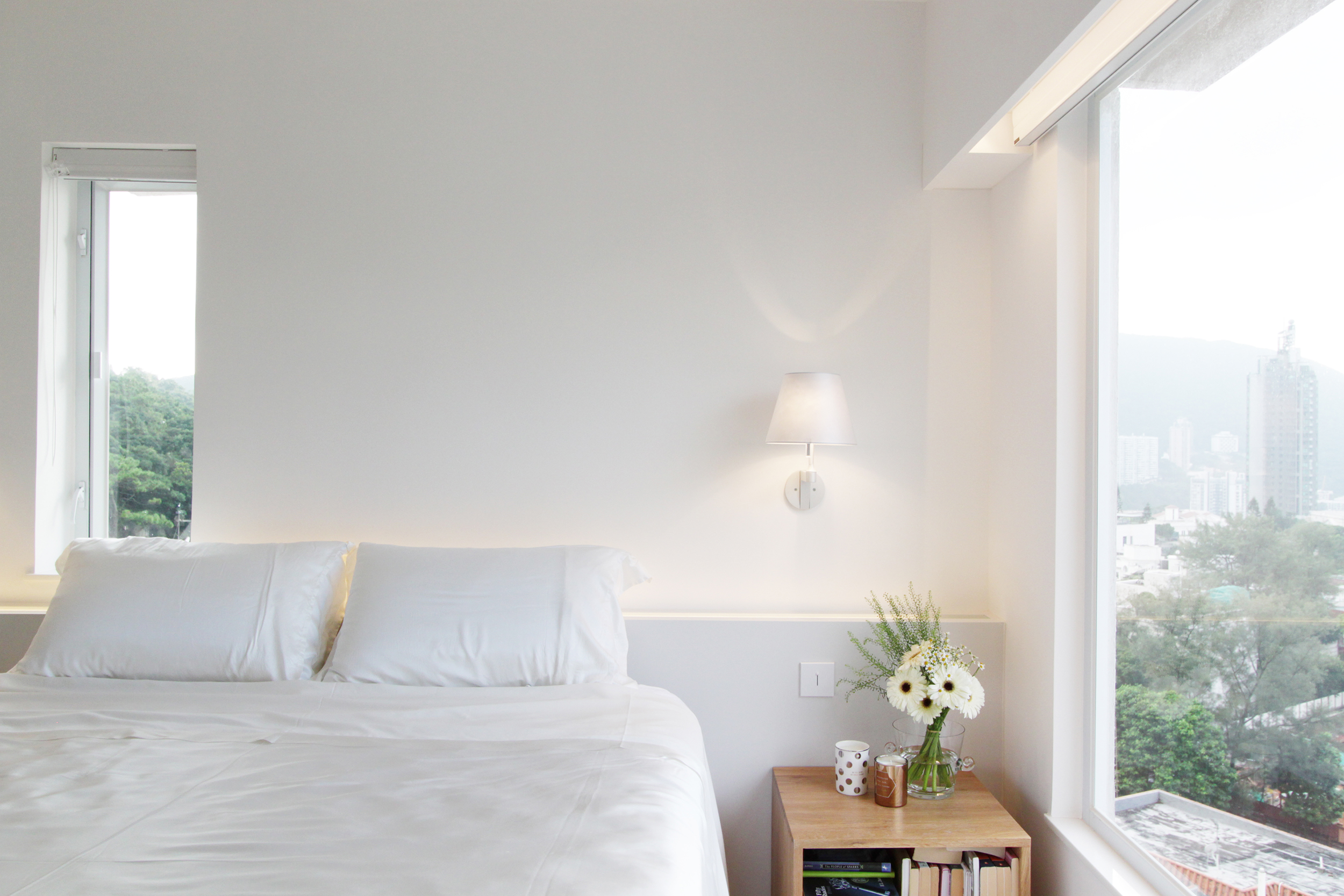 Master Bedroom | Headboard with integrated uplight and dimmable wall-lights help create a relaxing and zen ambiance as night falls. Large windows framing the views of Jardine's Lookout and the harbour.
