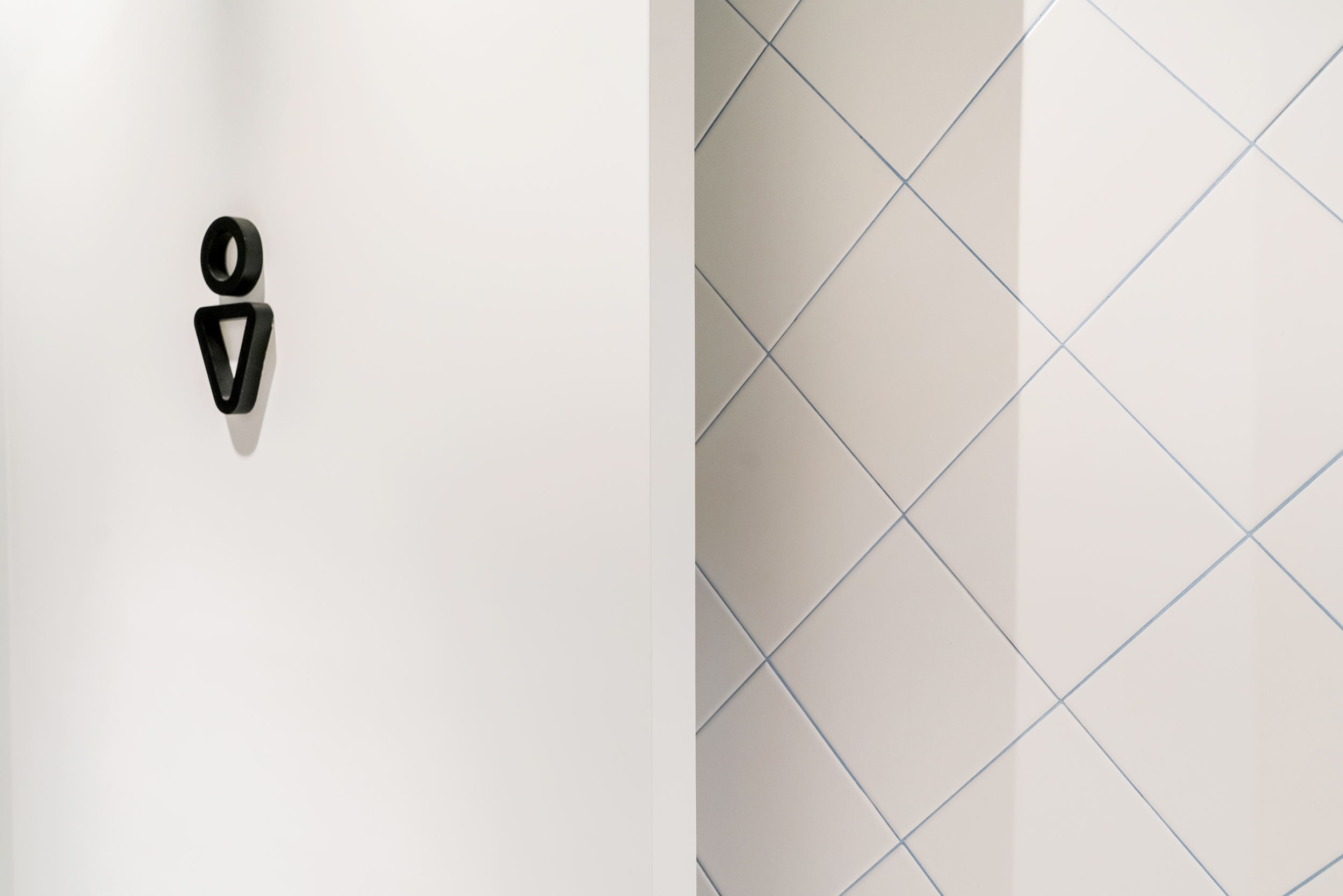 Washroom details. The use of coloured grout against the white tiles create playfulness in a subtle manner.