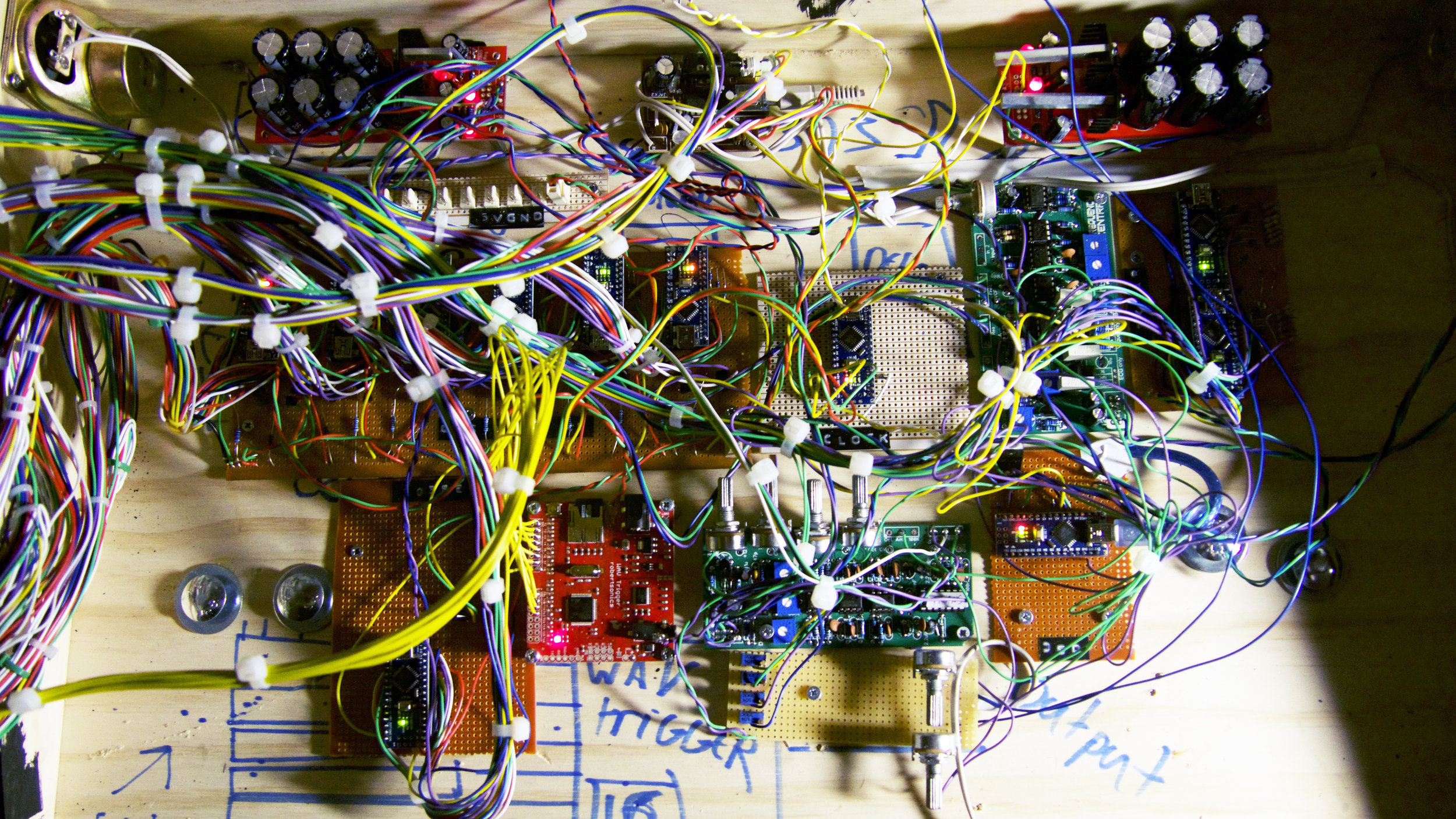 Spaghetti junction 12 Arduino NANOS, 4 Frequency Central Boards, 1 Sparkfun WAV trigger and a whole load of stripboard circuits.