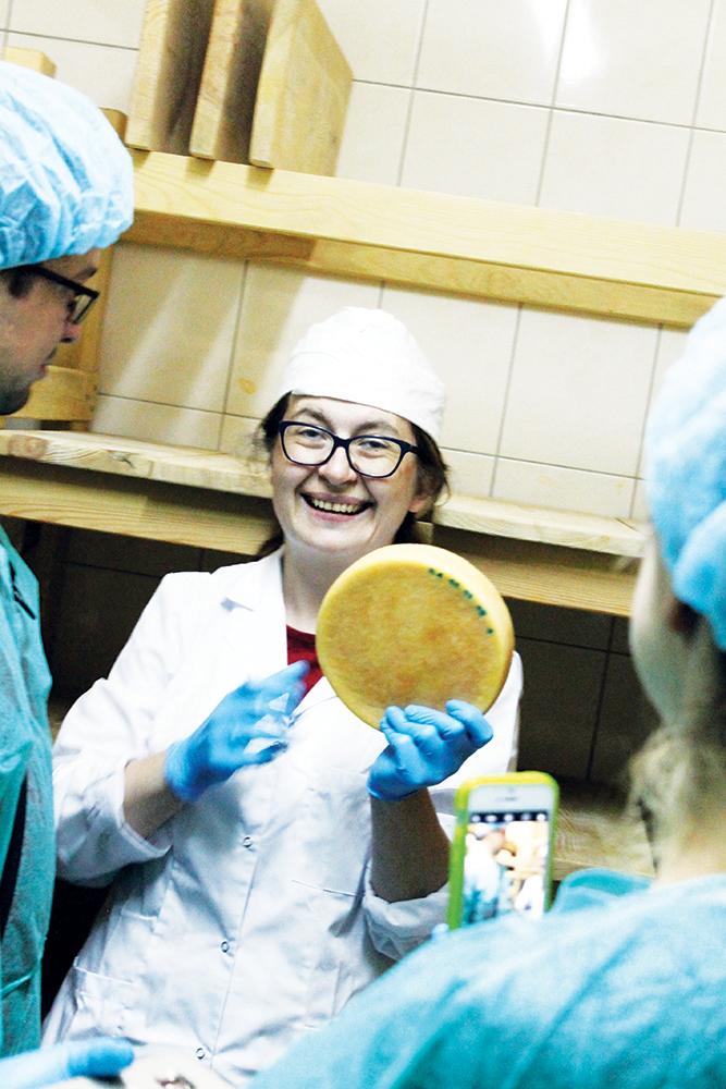 I YSTERIET: Lidka Waligorska, som er en av omsorgspersonene på gården, forteller oss om lagring av ost. Foto: Hedda Bjerén