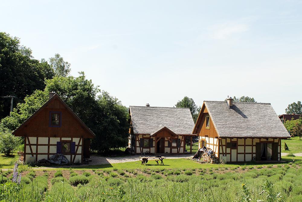 LAVENDELGÅRD: Disse tre husene har paret fått bygget på eiendommen sin. Husene leies ut til overnattingsgjester. Frokosten nytes gjerne på benken utenfor på fine sommerdager. Foto: Tenk Koffert