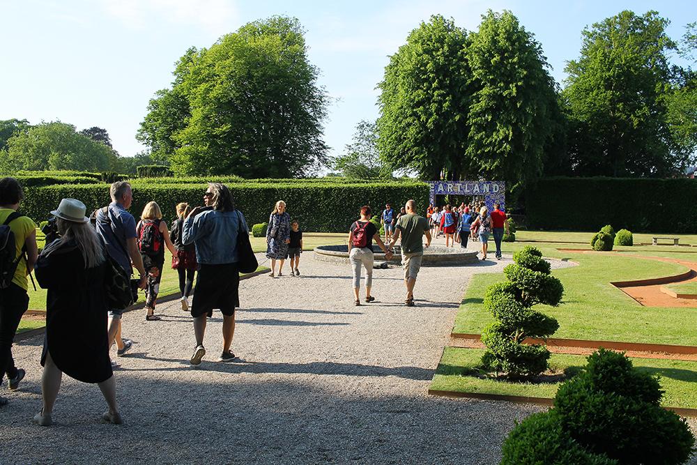 INNGANGEN: Til venstre ligger slottet, og rett fram er inngangen til festivalen. Legg merke til de eventyrlige, små trærne utenfor! Foto: Tenk Koffert