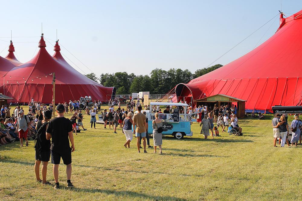 """MER ENN MUSIKK: I disse store, røde teltene er det """"talks"""", eller foredrag, med mange spennende personligheter. Noen av foredragene var så populære at det ikke var nok sitteplasser til alle, og folk lå utenfor, på gresset, med hodet innunder teltduken. Foto: Tenk Koffert"""