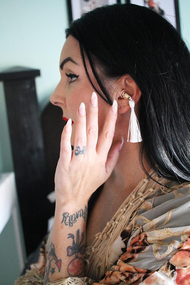 HVITE: De hvite, fine øreproppene ser ut som øredobber. Foto: Tenk Koffert