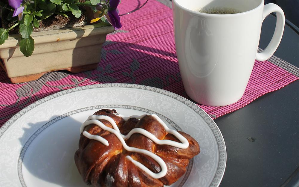 HJEMMEBAKT: Sissel er god på å bake. Det smakte nydelig med kaffe og hjemmelaget kanelbolle i sola utenfor et av Munkebys gamle, fine bygg. Foto: Tenk Koffert