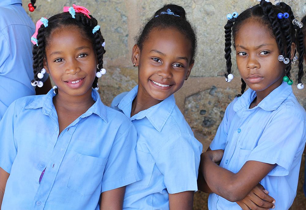 DEN DOMINIKANSKE REPUBLIKK: Jeg møtte mange glade, vakre mennesker i Den dominikanske republikk. Her er tre skolejenter som venter på å komme inn på et museum. Foto: Tenk Koffert