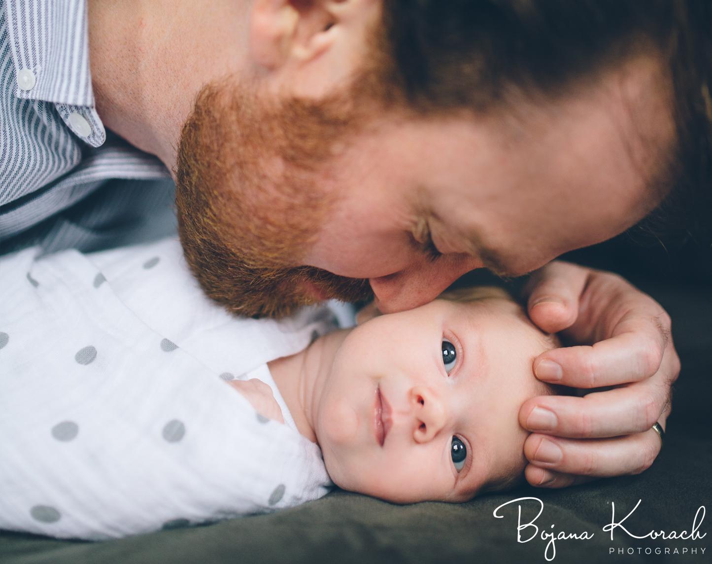father and newborn cuddling