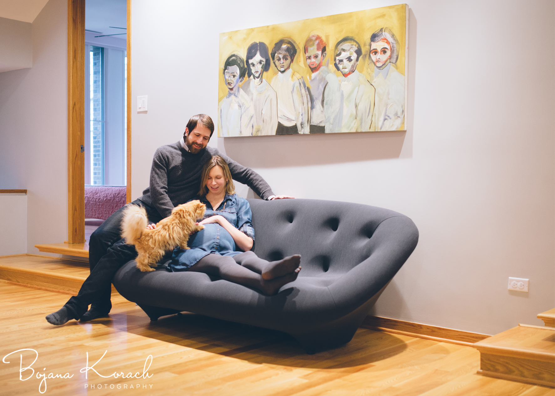 expecting couple with a cat in a wright inspired home
