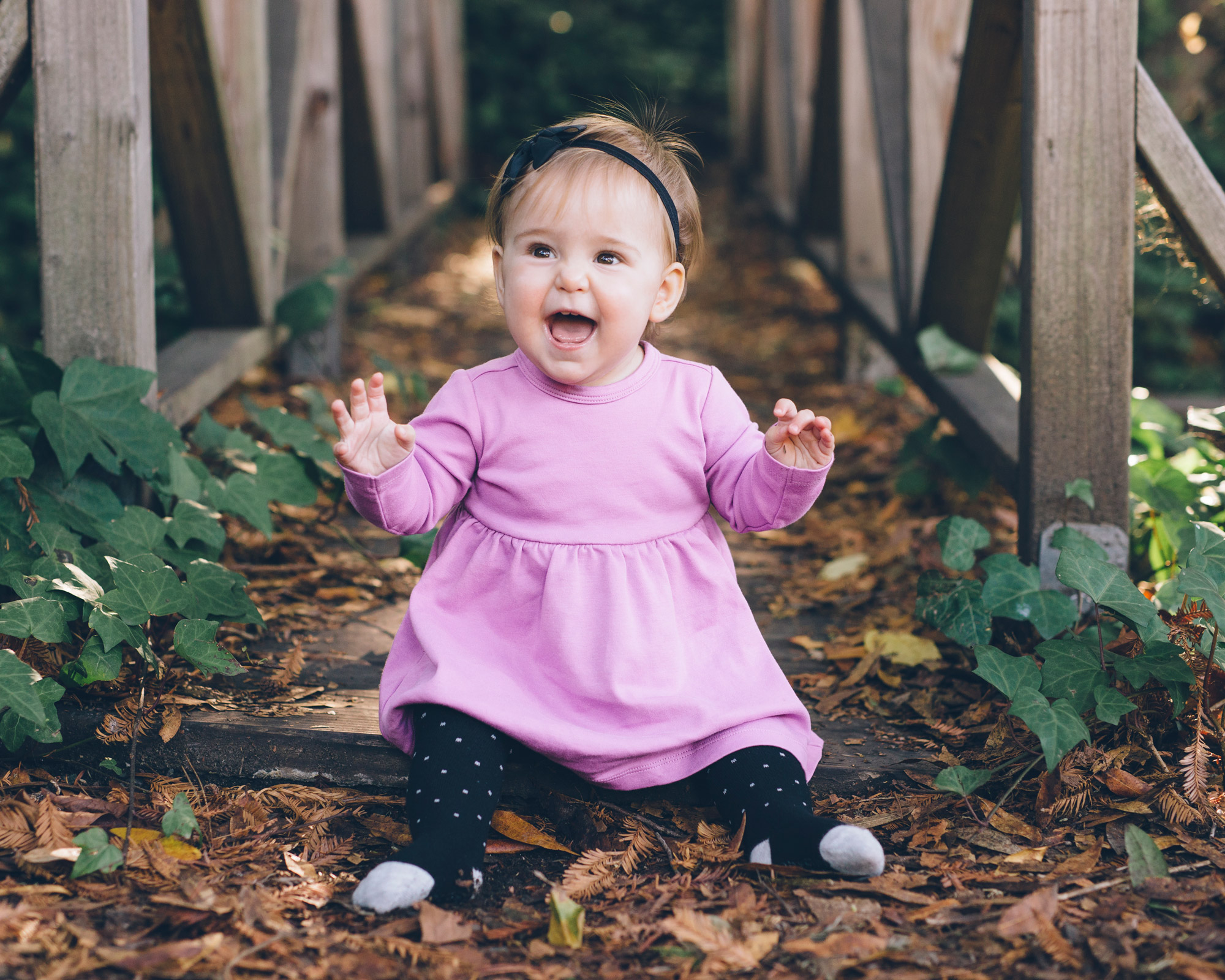 baby-girl-sitting-and-smiling-on-leaves.jpg