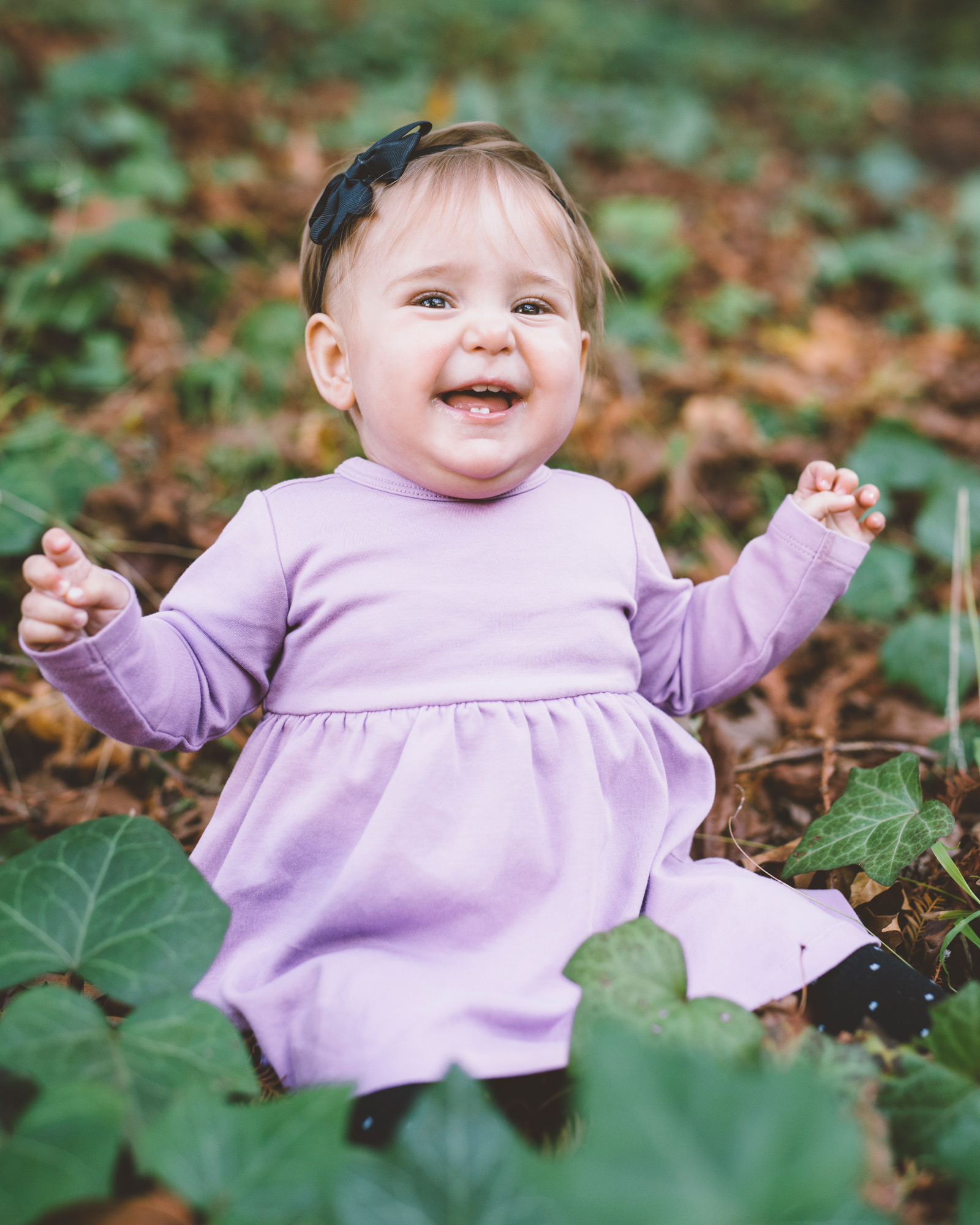 baby-girl-sitting-in-the-ivy-and-smiling.jpg