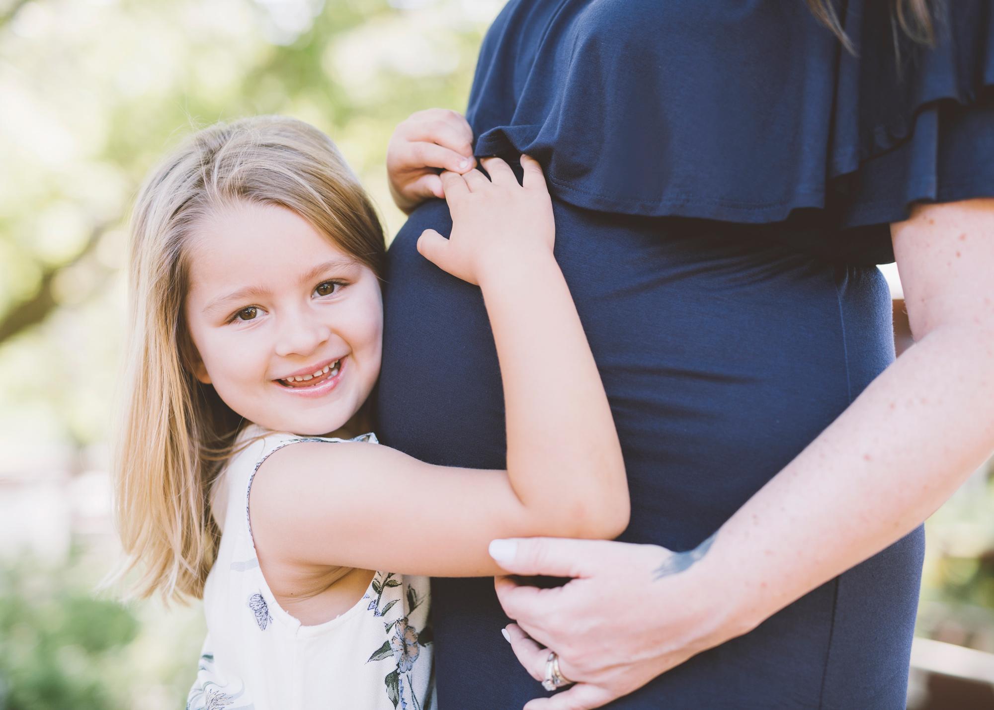 big-sister-hugging-mother's-pregnant-belly.jpg
