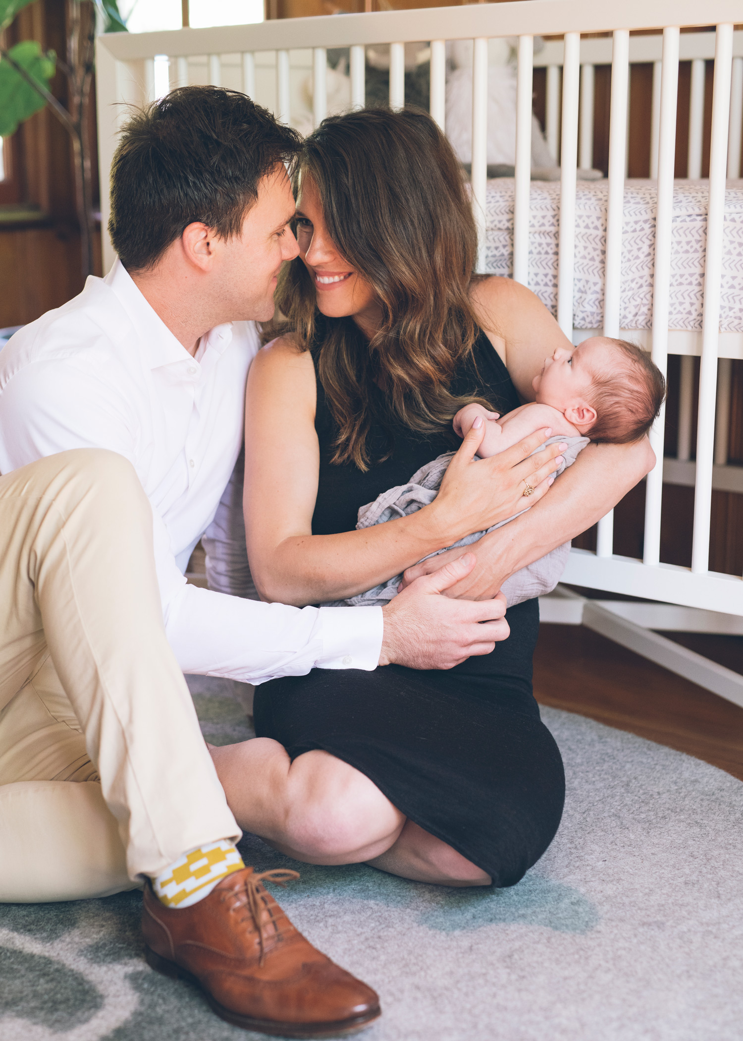 new-parents-gazing-at-each-others-eyes-while-holding-a-newborn-boy.jpg