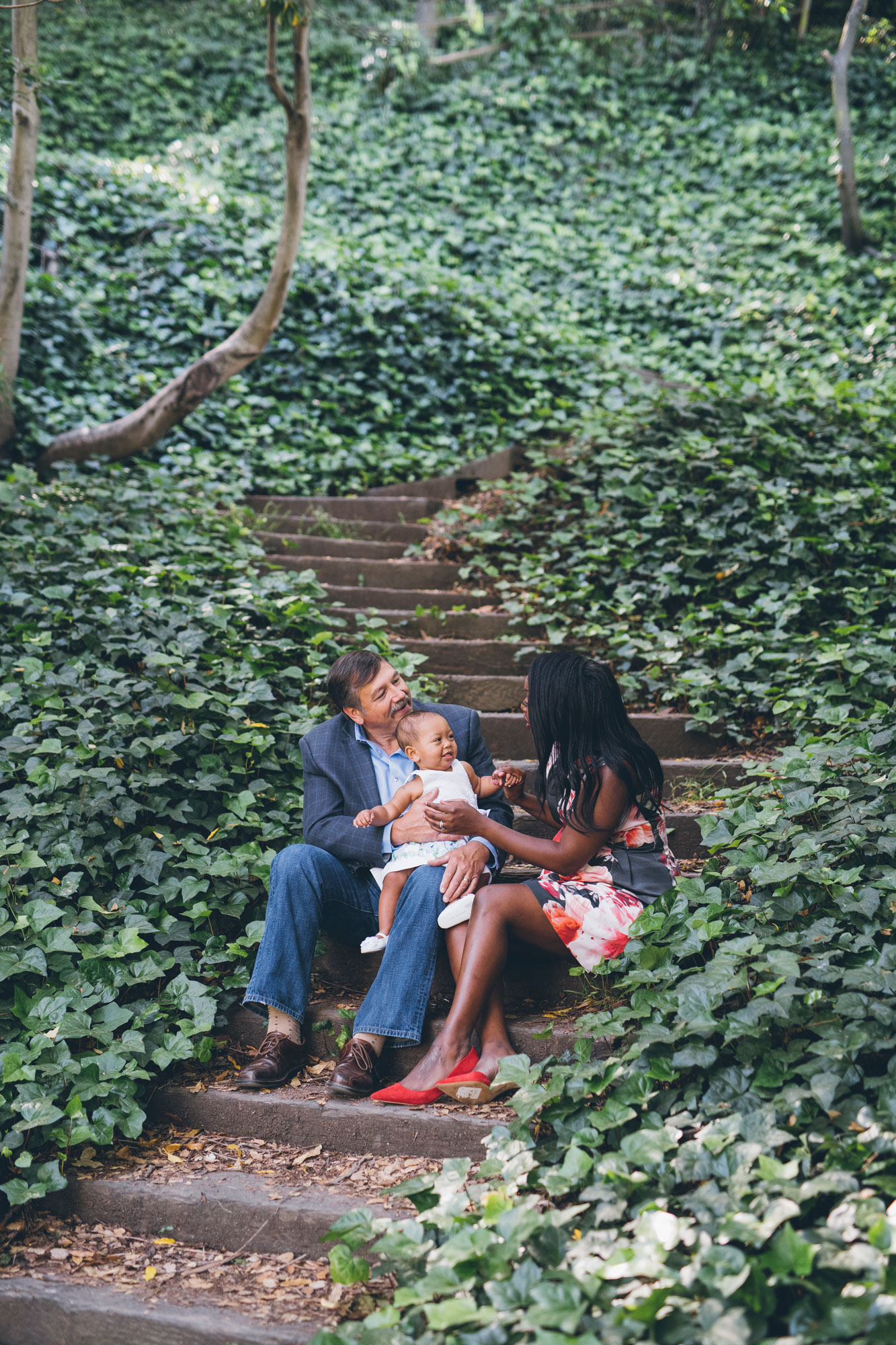 family-of-three-sitting-on-wooden-steps-in-the-wooded-area.jpg