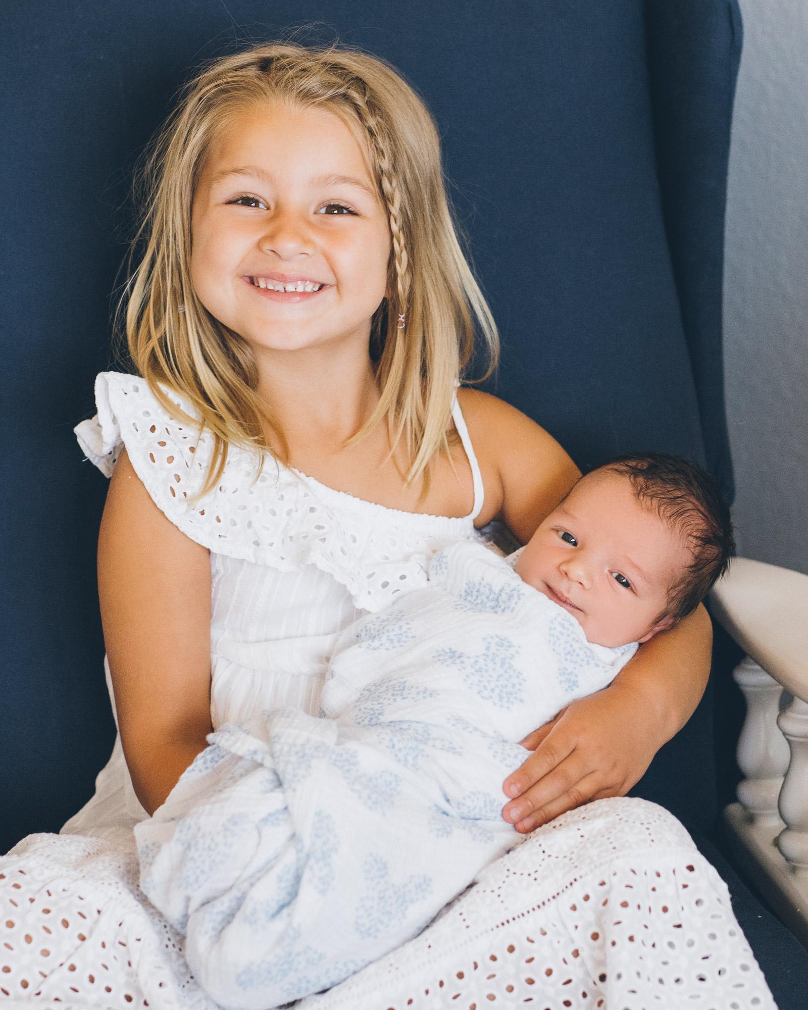 big-sister-holding-newborn-baby-brother.jpg