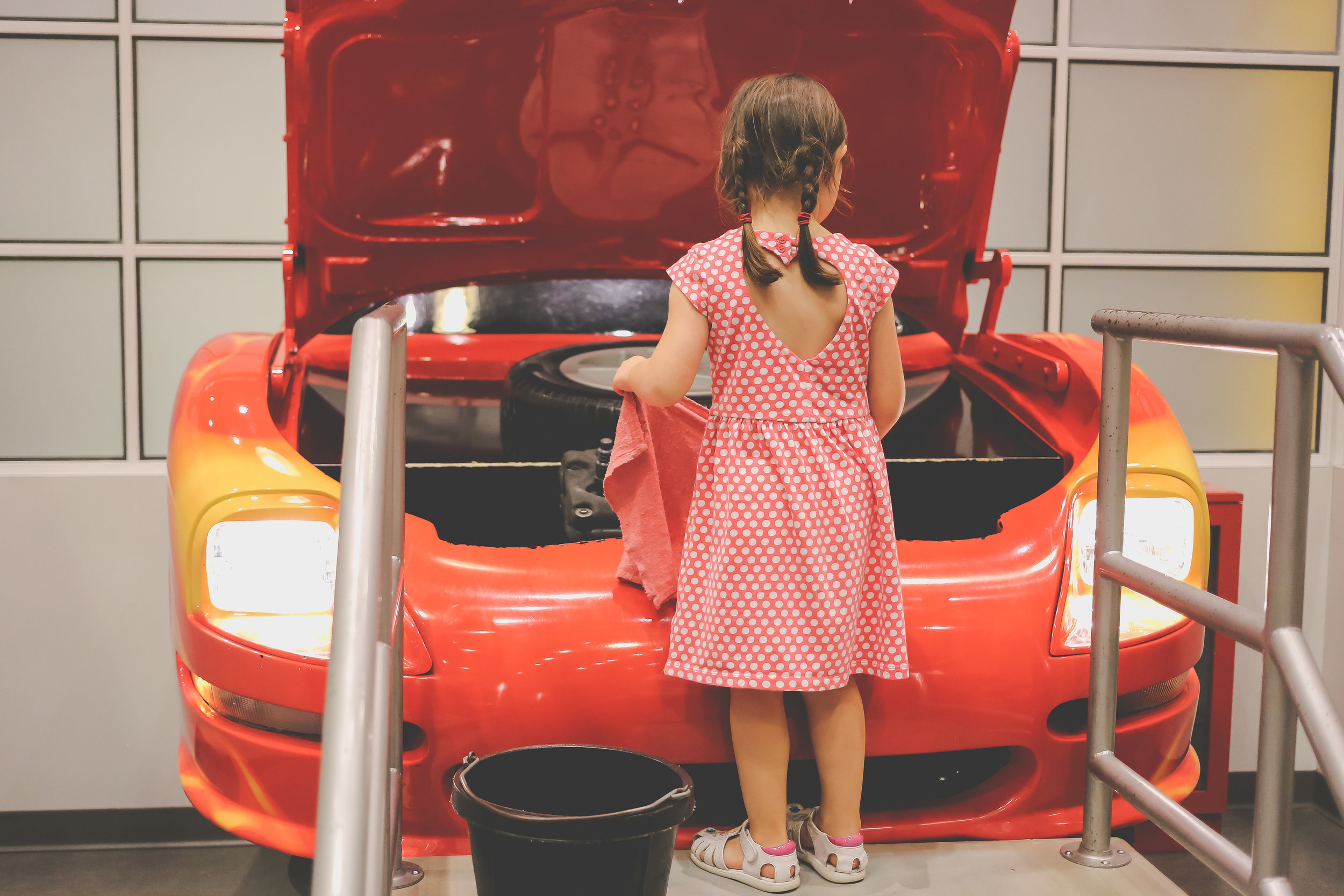 Playing mechanic at the Please Touch Museum in Philadelphia. Pennsylvania Documentary Child Photogaphy.