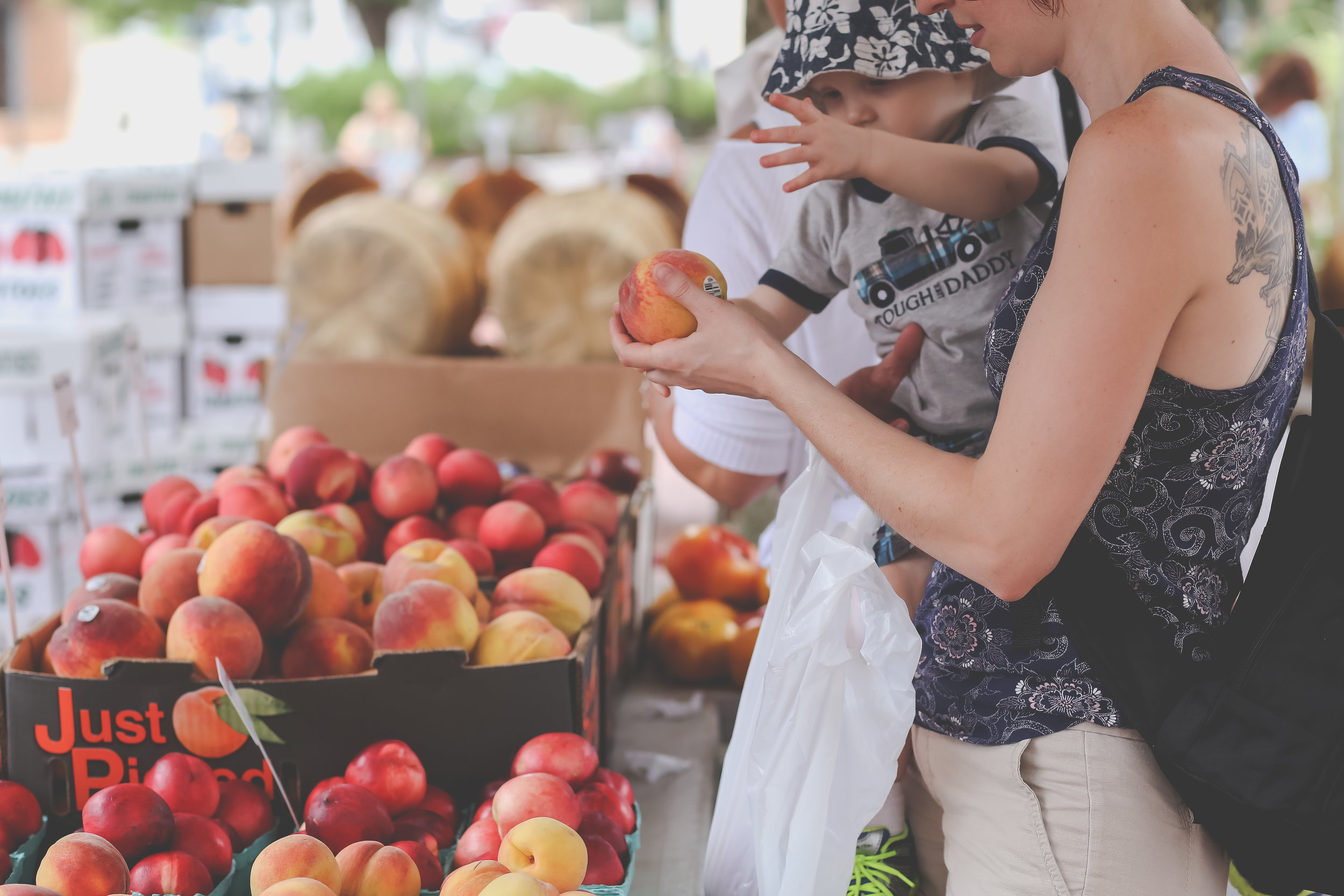 Mother and son buying peaches at the farmer's market in Rutherford, NJ. Staten Island family photographer.