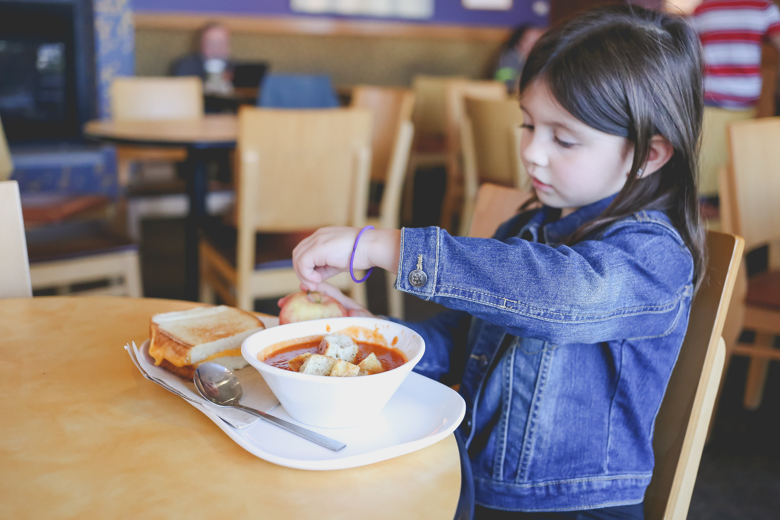Girl eating grilled cheese and tomato soup at Panera Bread in Staten Island, NY. On location family photo session.