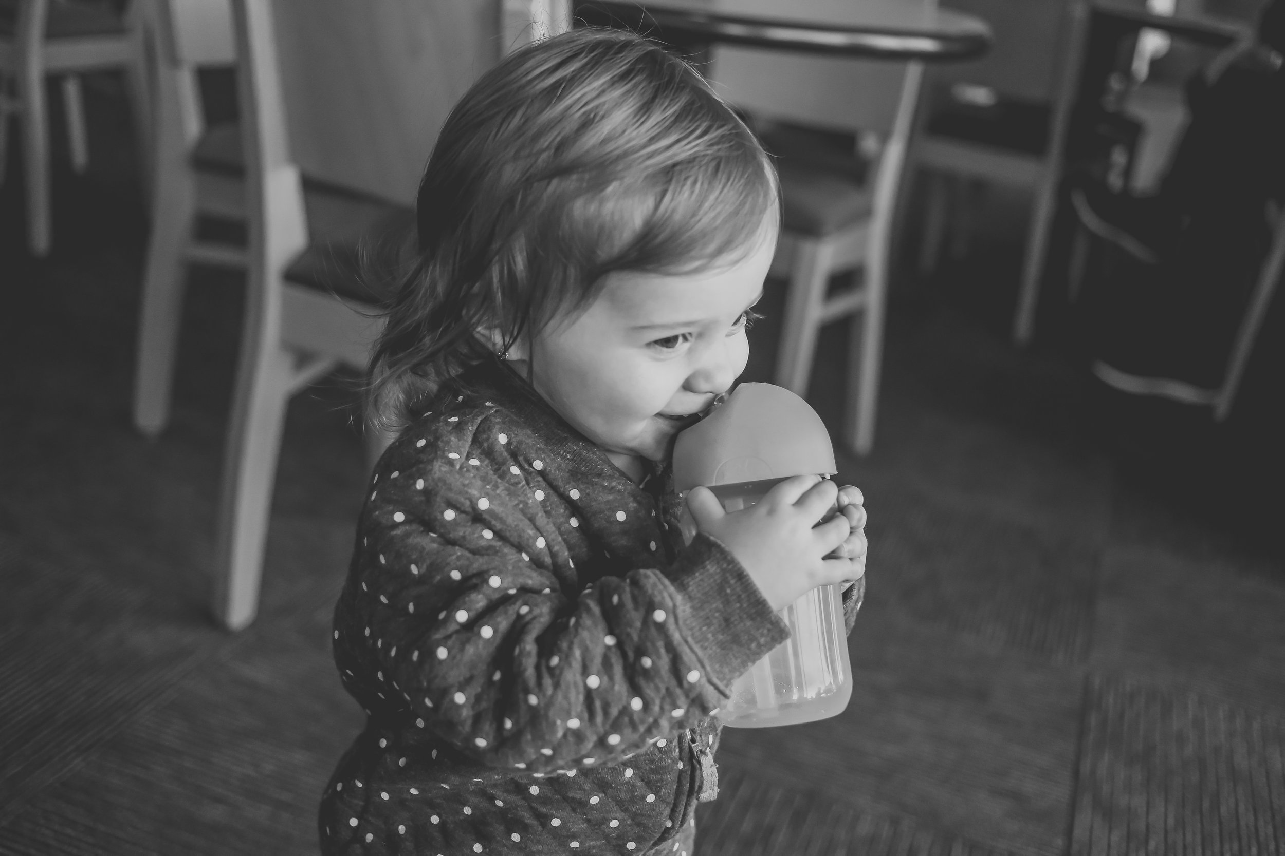 Toddler girl drinking from her cup at Panera Bread in Staten Island, NY. Documentary family photography.