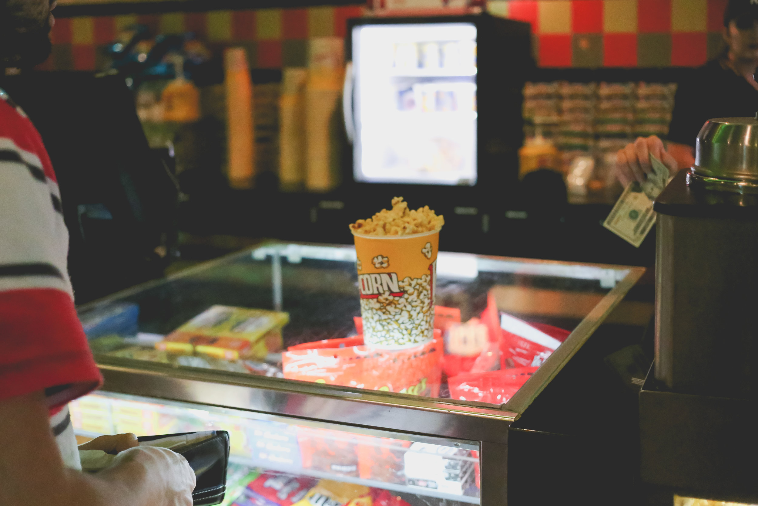 Buying popcorn at The Atrium movie theater in Staten Island, NY. Family Photojournalism.