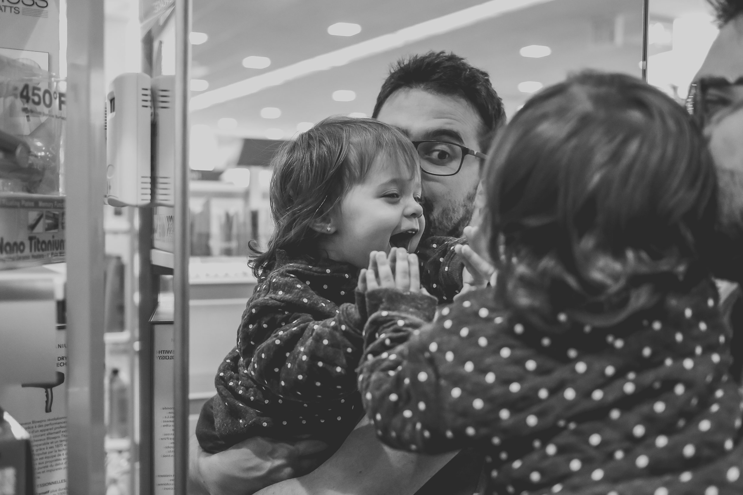 Playing in the mirror at Ulta beauty supply store in Staten Island, NY. Storytelling Family Photography.
