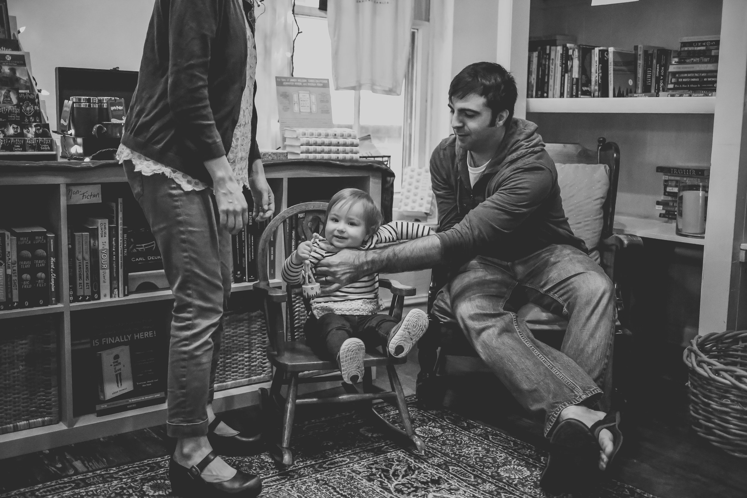 A father helping his daughter into a chair at Let's Play Books in Emmaus, PA. Lehigh Valley Documentary Family Photography.