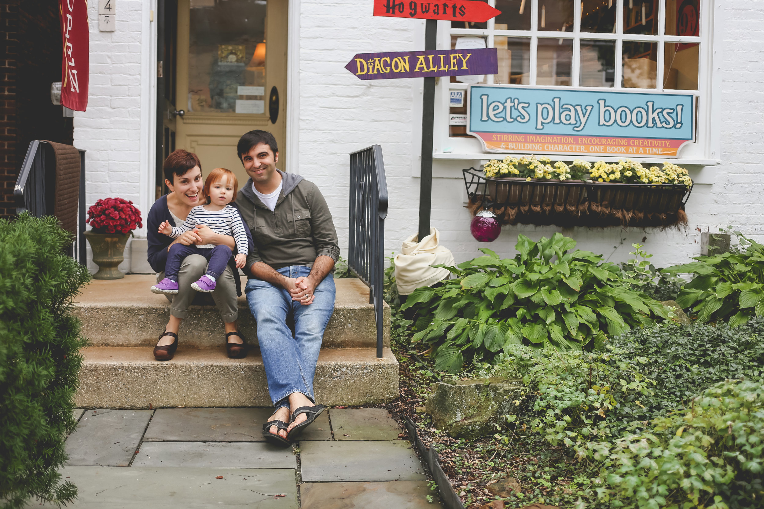 Family sitting on the steps of Let's Play Books on Main St. Emmaus, PA Family Photography.