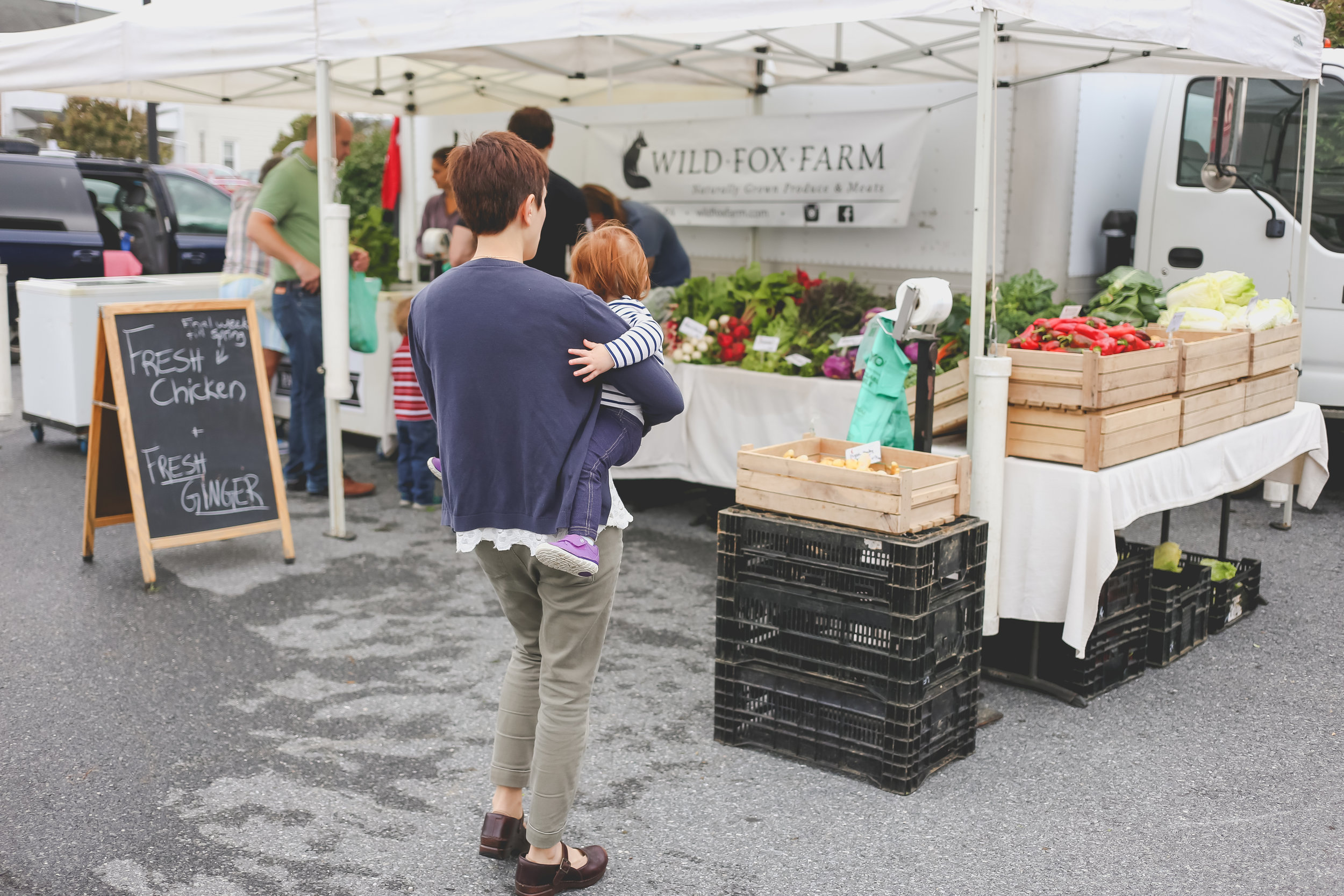 Mother with baby at the Emmaus Farmer's Market, Pennsylvania. Lehigh Valley Documentary Family Photographer.