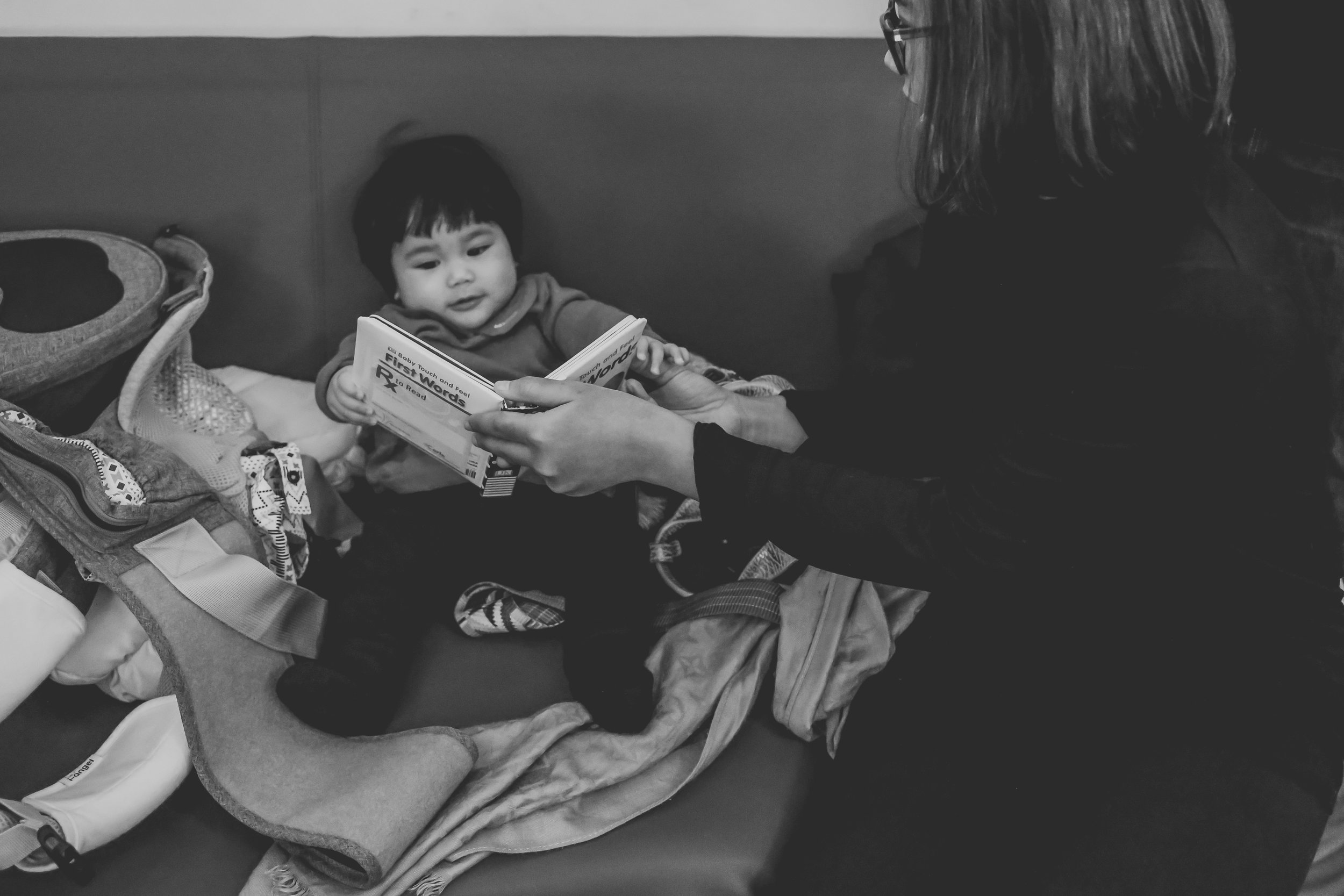 Baby reading with her mother at the New York Public Library at 42nd Street during a documentary family session by Jen Grima Photography.
