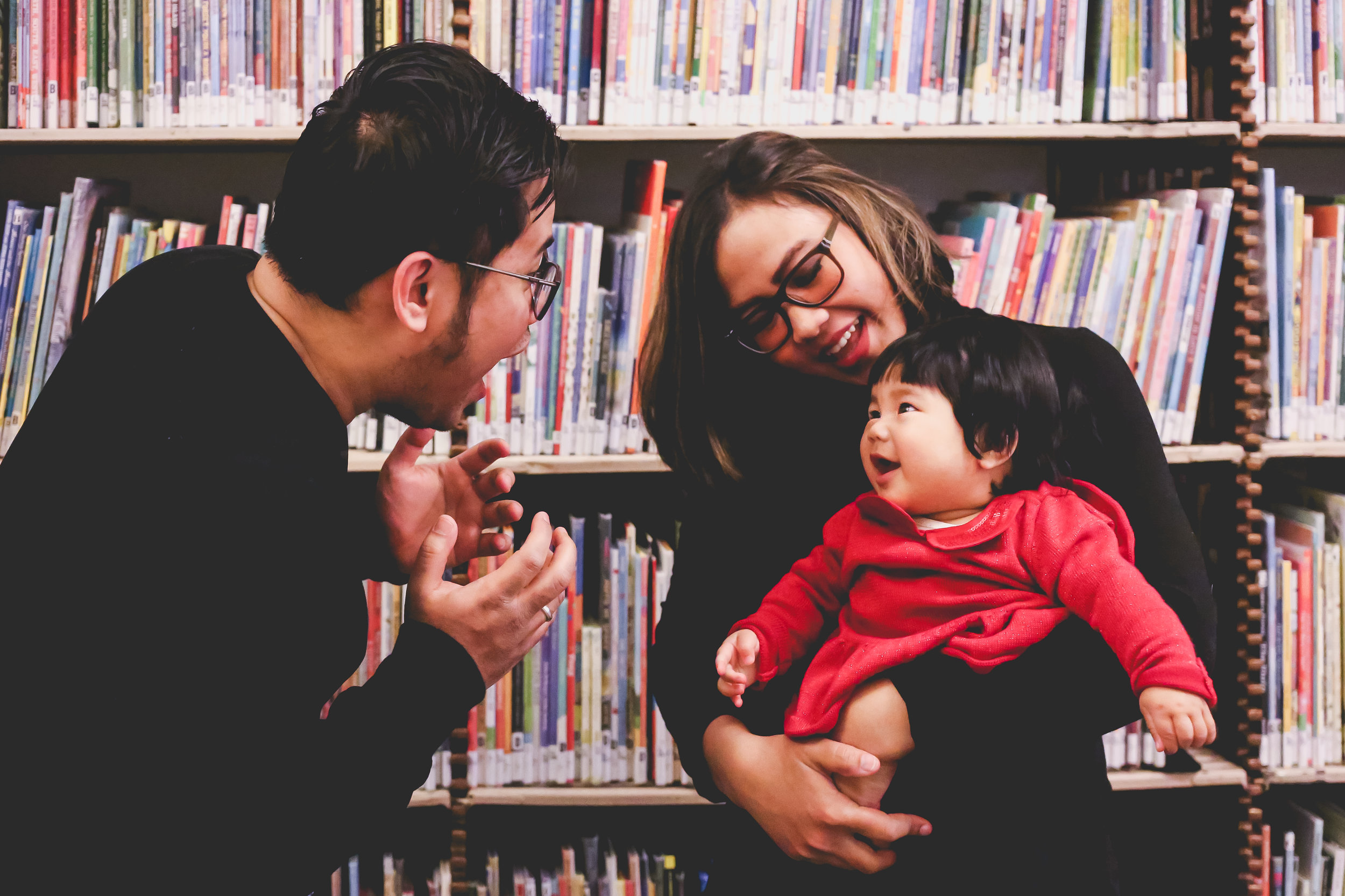 Young family playing peek-a-boo at the library, Manhattan. New York City vacation photography by Jen Grima, Lehigh Valley family photographer.