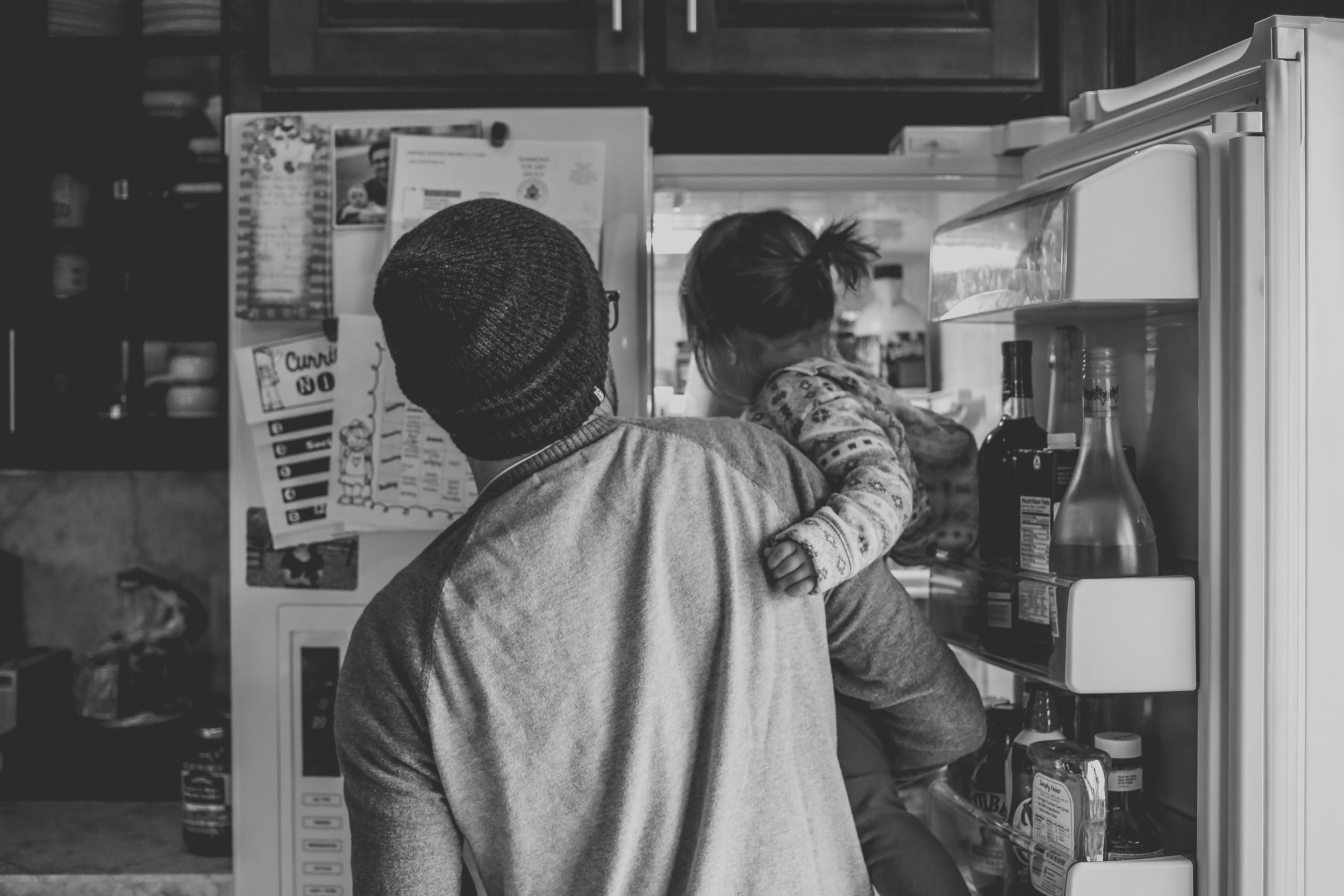 Little girl with dad checking the refrigerator for a snack during an unposed family photography session, Lehigh Valley, PA.