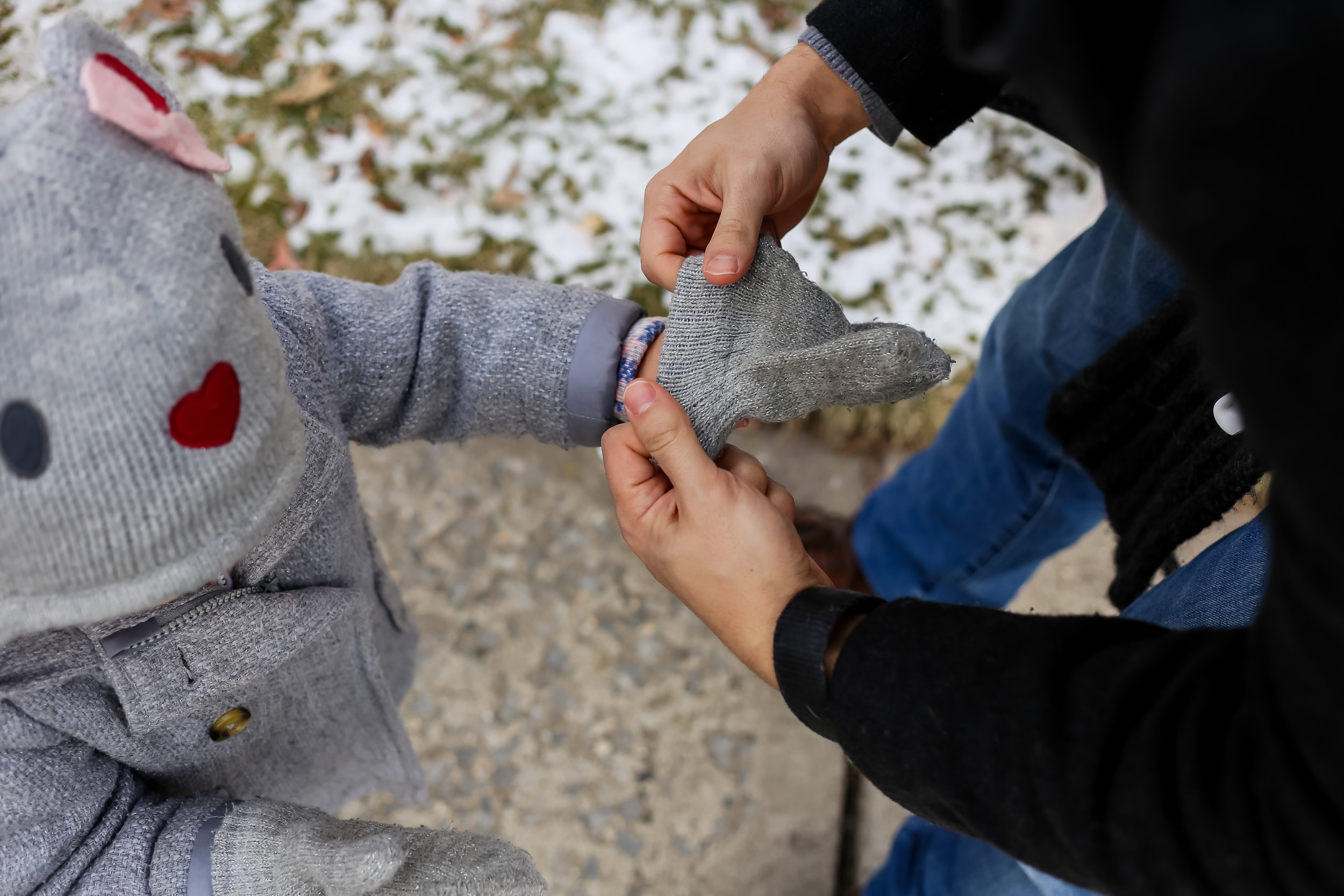 A father helping his daughter on with her mittens. Documentary family photography by Jen Grima of Lehigh Valley, Pennsylvania.