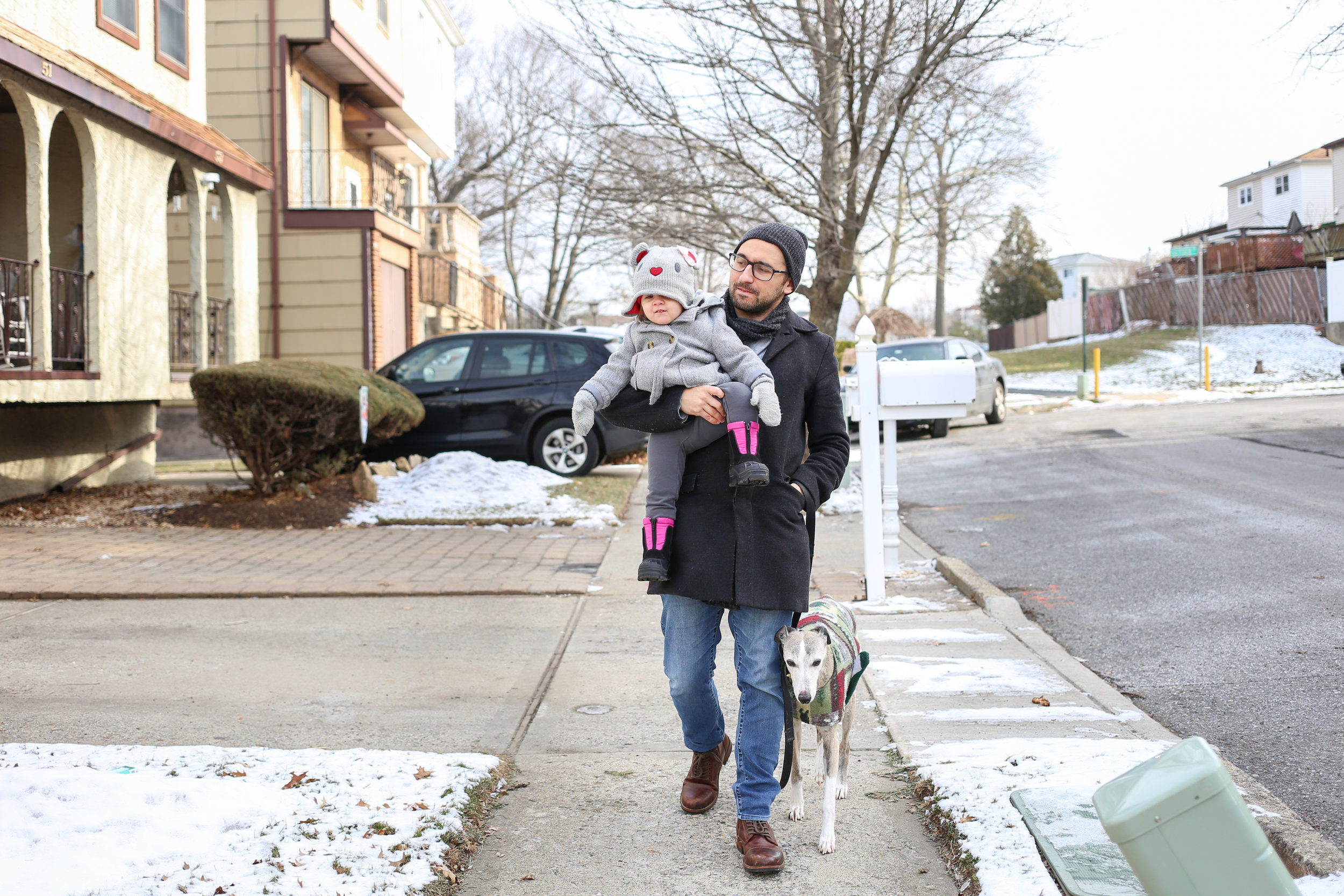 Dad carrying his baby daughter while walking the dog. Pennsylvania family photography.