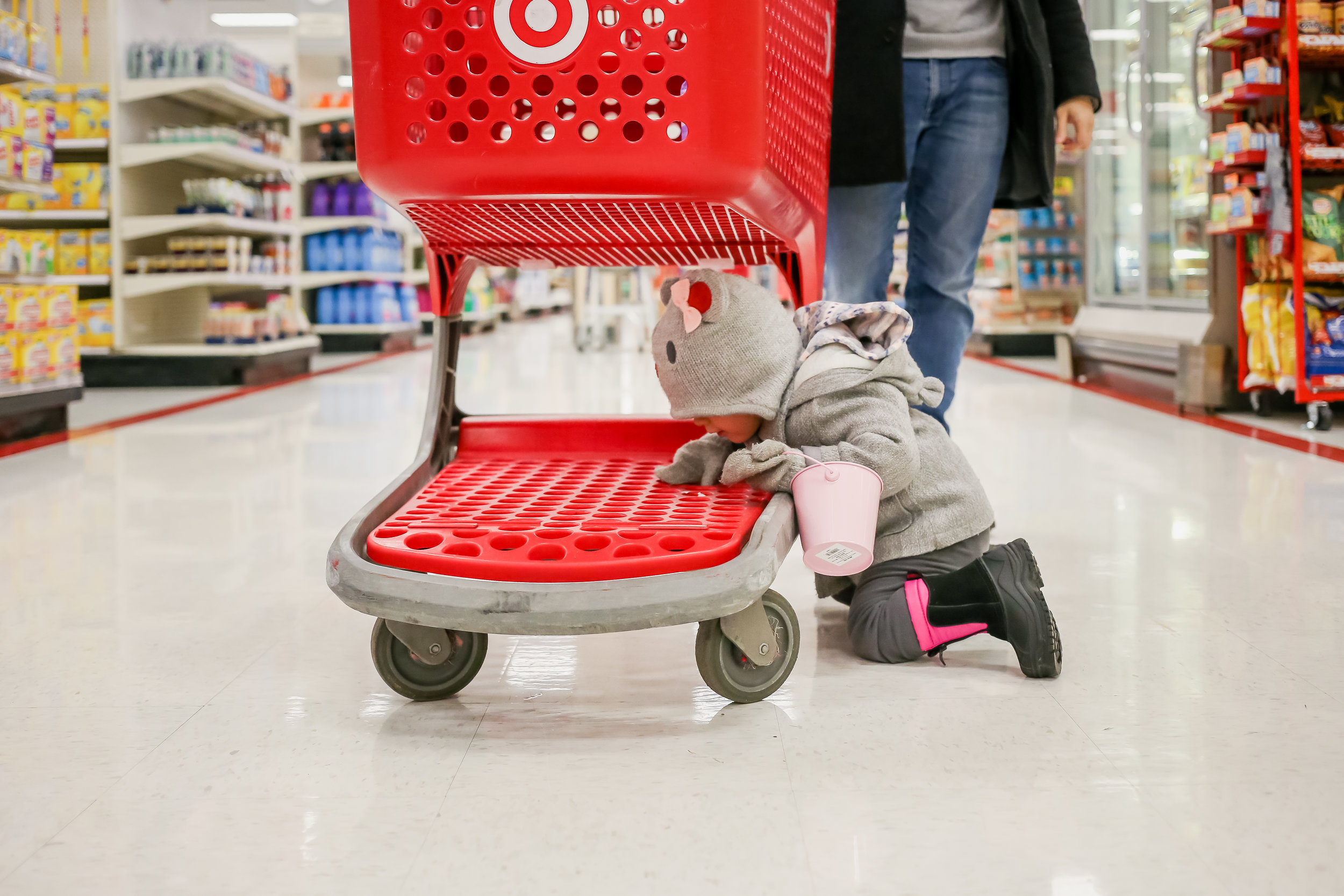 Toddler girl under the cart while shopping at Target during a family photography session. Day in the Life photography in Lehigh Valley, Pennsylvania.