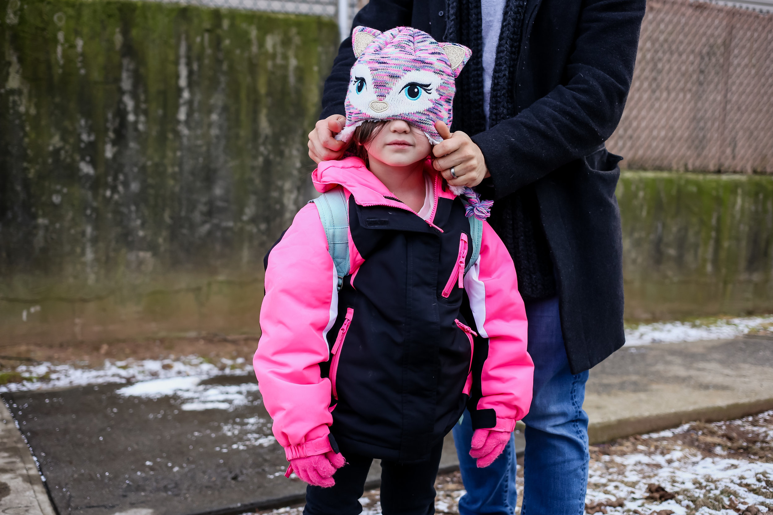 Young girl with winter hat and backpack, coming home from school.