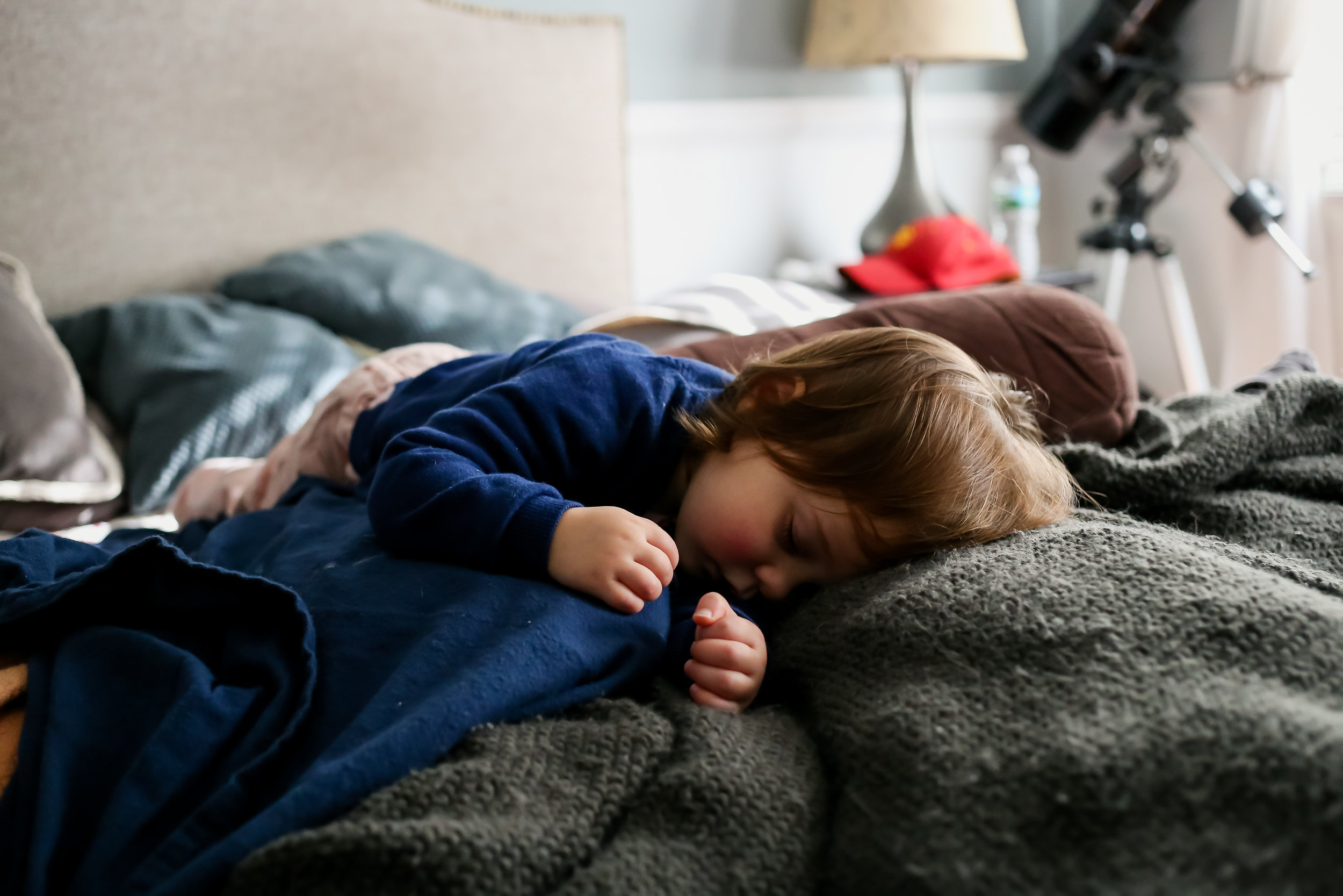 Two year old girl taking a nap on mom and dad's bed. At home candid family photography in Allentown, PA.