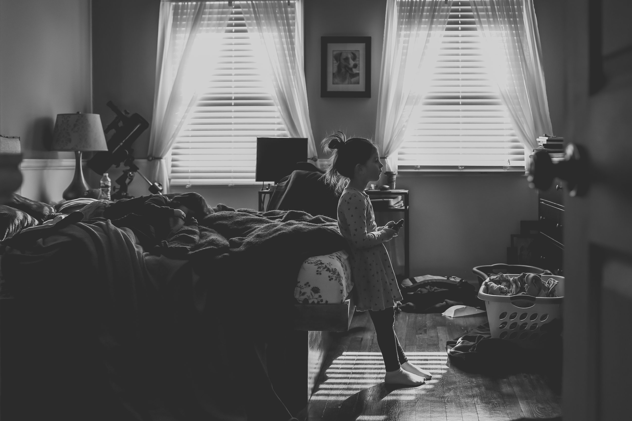 Young girl watching TV in her parents room, at home documentary family photography session by Jen Grima, Lehigh Valley, PA.