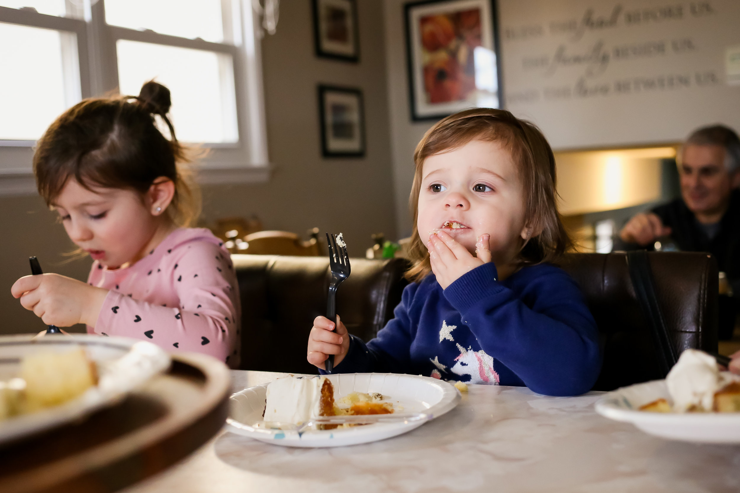 Two year old girl eating her birthday cake. Unposed family photo session by Jen Grima Photography, Lehigh Valley.